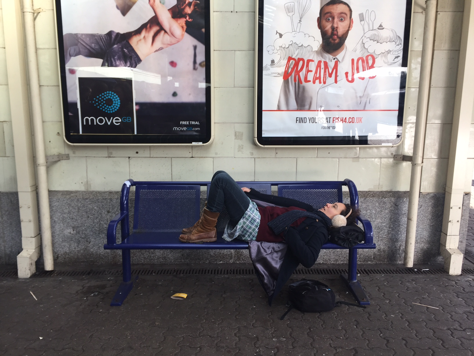 Centre of the image is a blue bench with a lady laying down on it with two billboard posters on the wall behind her