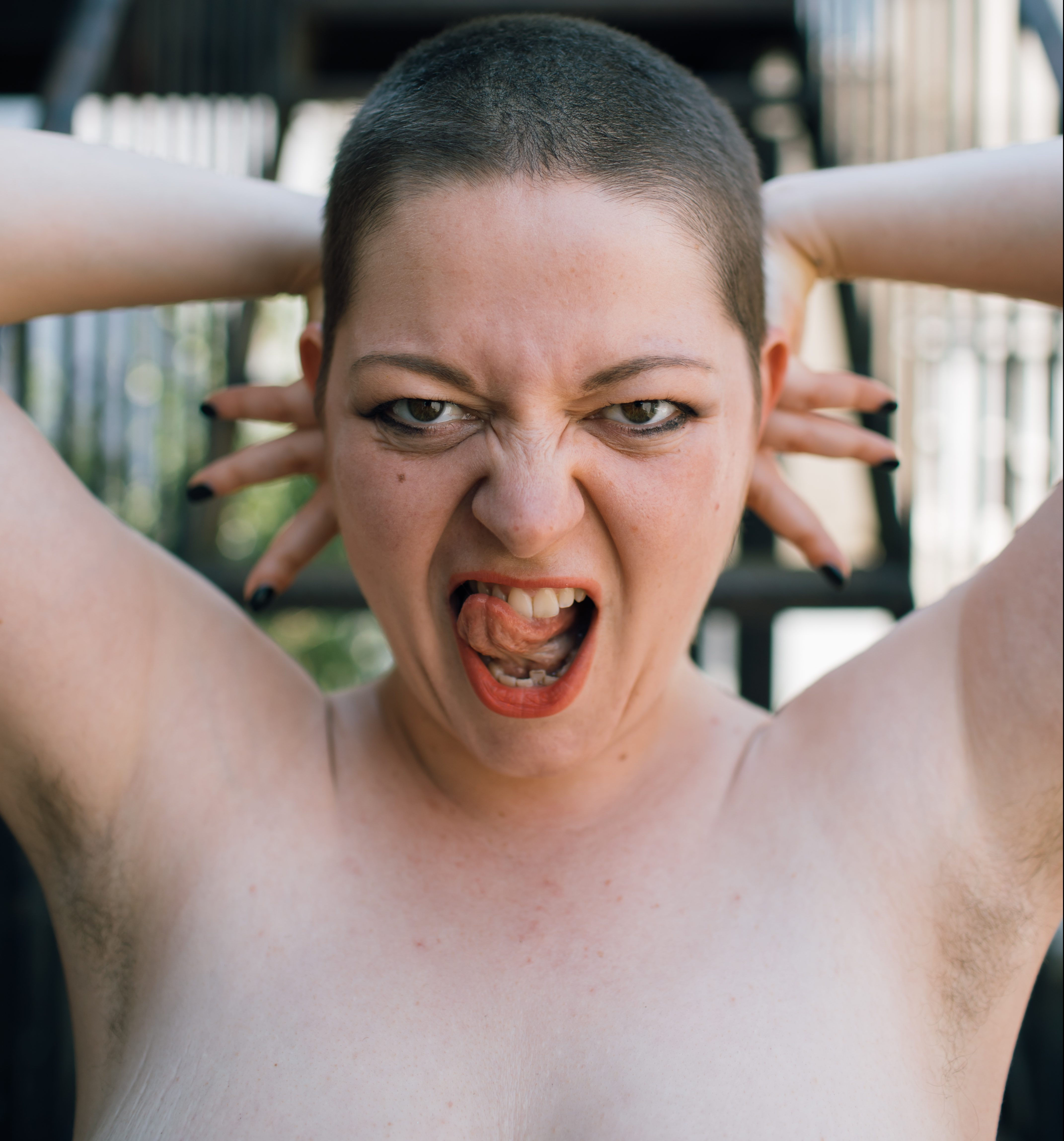 A topless woman holds her arms up and sticks her tongue out at the camera