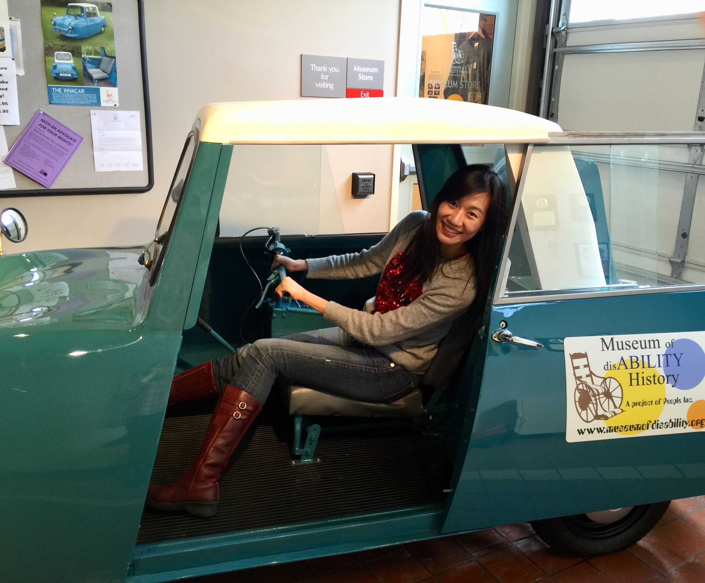 Sandie Yi at Museum of Disability History sits in a blue car with the door open smiling at the camera
