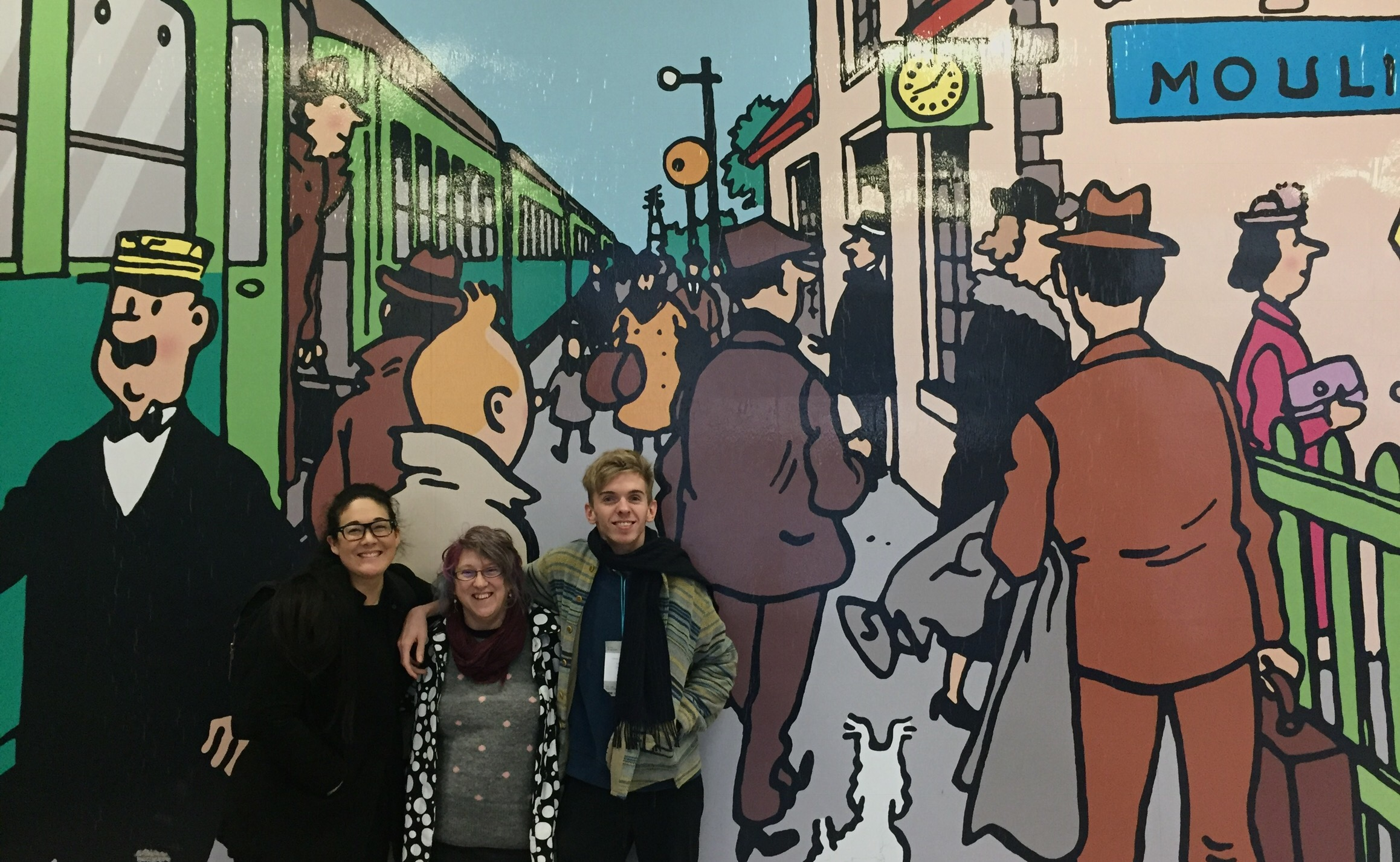 3 people, 2 women on the left and 1 man on the right stand in front of a painted wall. They are all smiling.