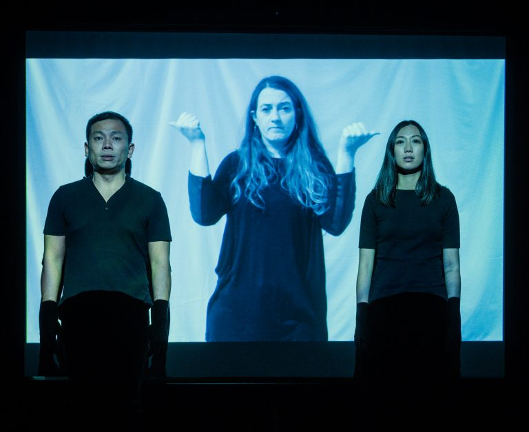 A man and a woman stand in front of a projection of a woman holding her two hands up in fists