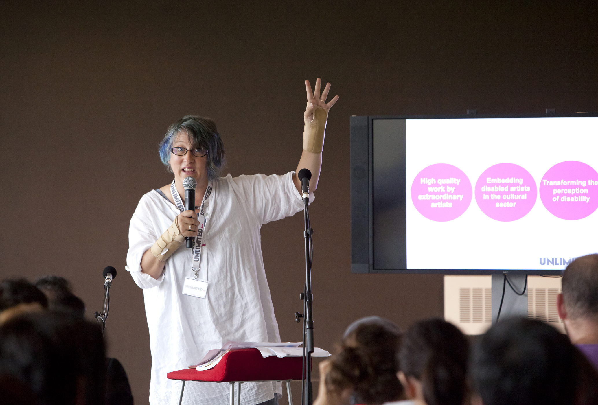 A woman ,giving a lecture , raising her hand as she talks into a microphone. There is a TV screen behind her with a power presentation on it