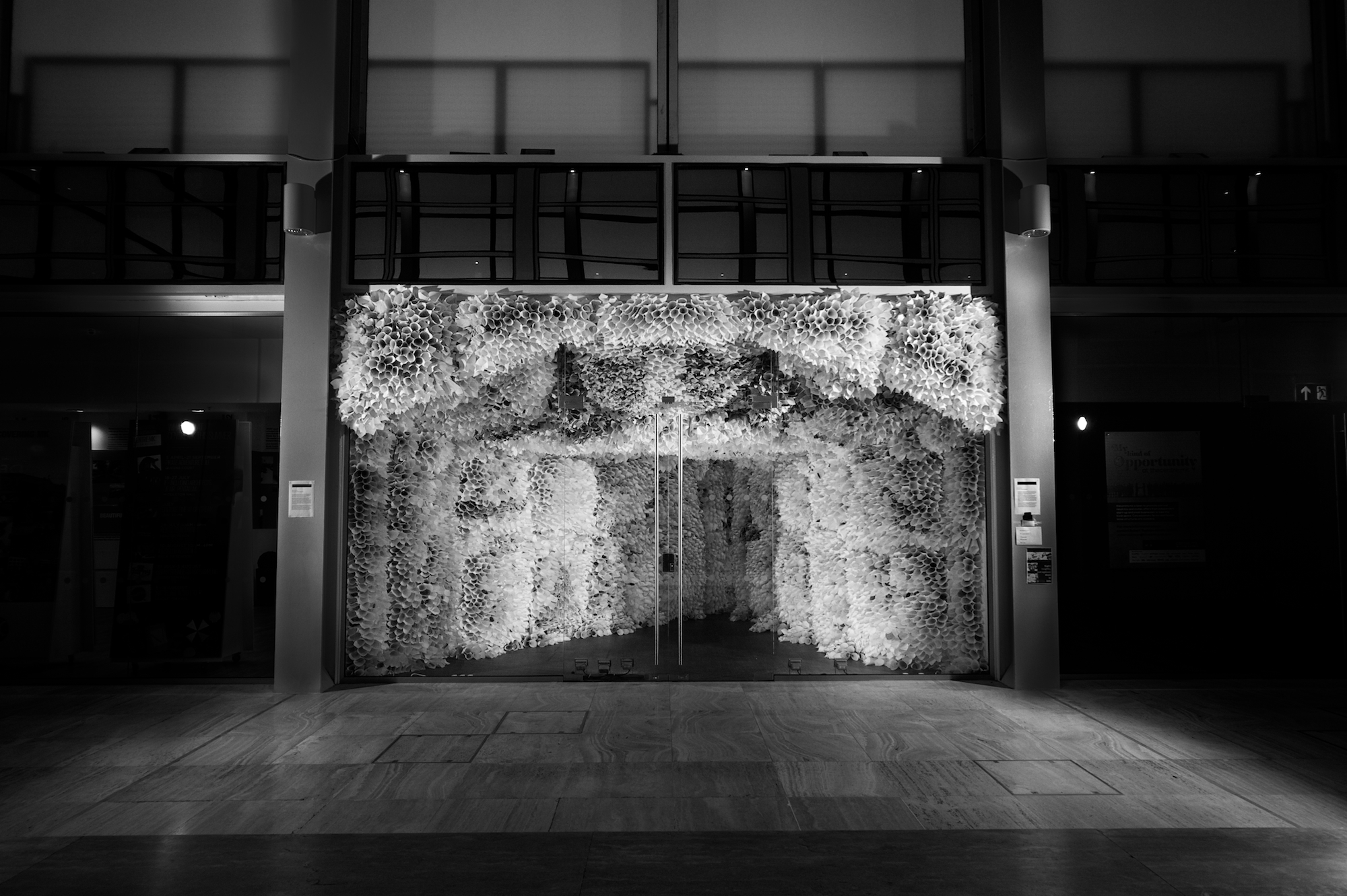 A glass door entering a corridor of thousand of white paper sculptures. leading to a grand entrance.