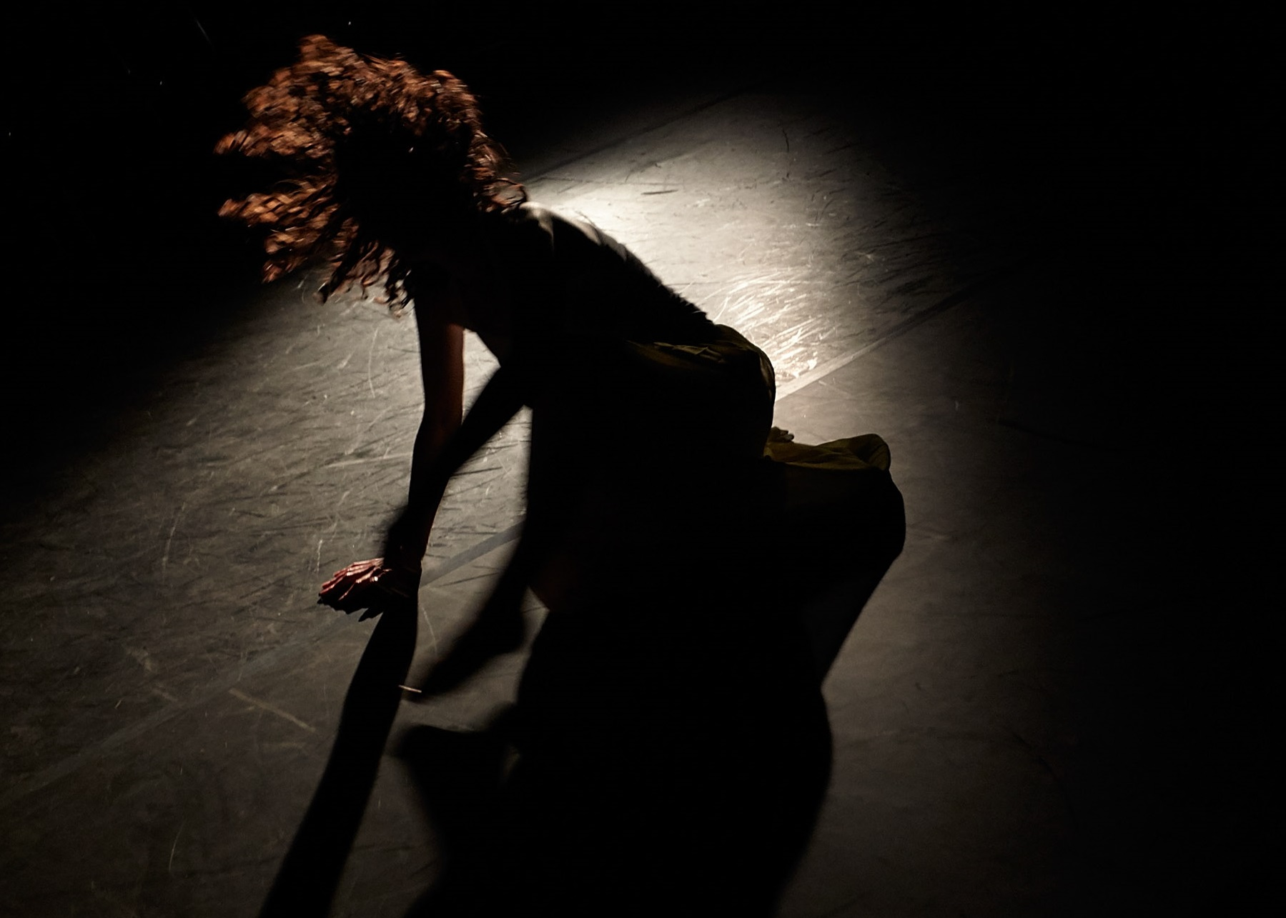 A woman crouching on the floor with a light shinging on her. Her face is hidden