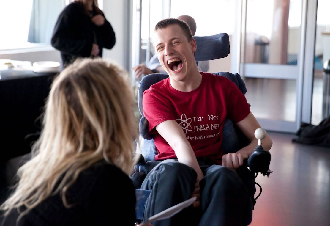 A young man having a conversation with a woman we cannot see. The young man is wearing a t-shirt and is in an electric wheelchair.