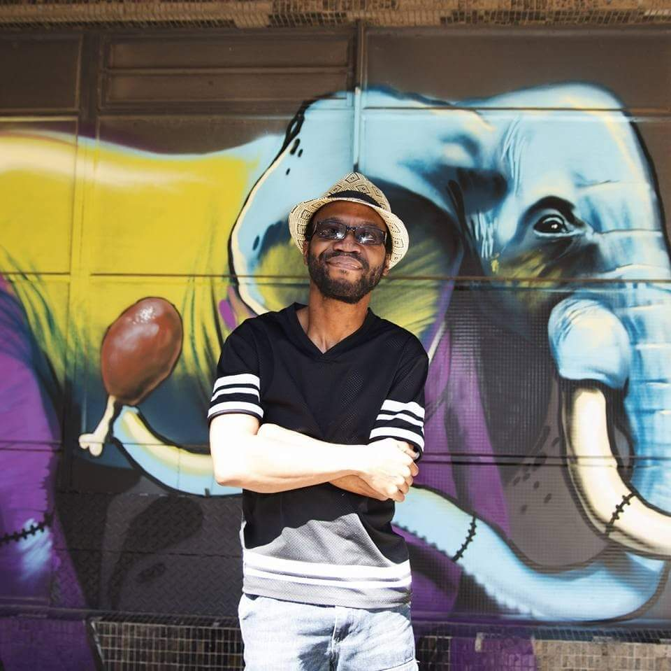 A black man posing in front of a wall which has a graffiti type drawing of an elephant. He is wearing a hat and sunglasses and has he's arms folded.