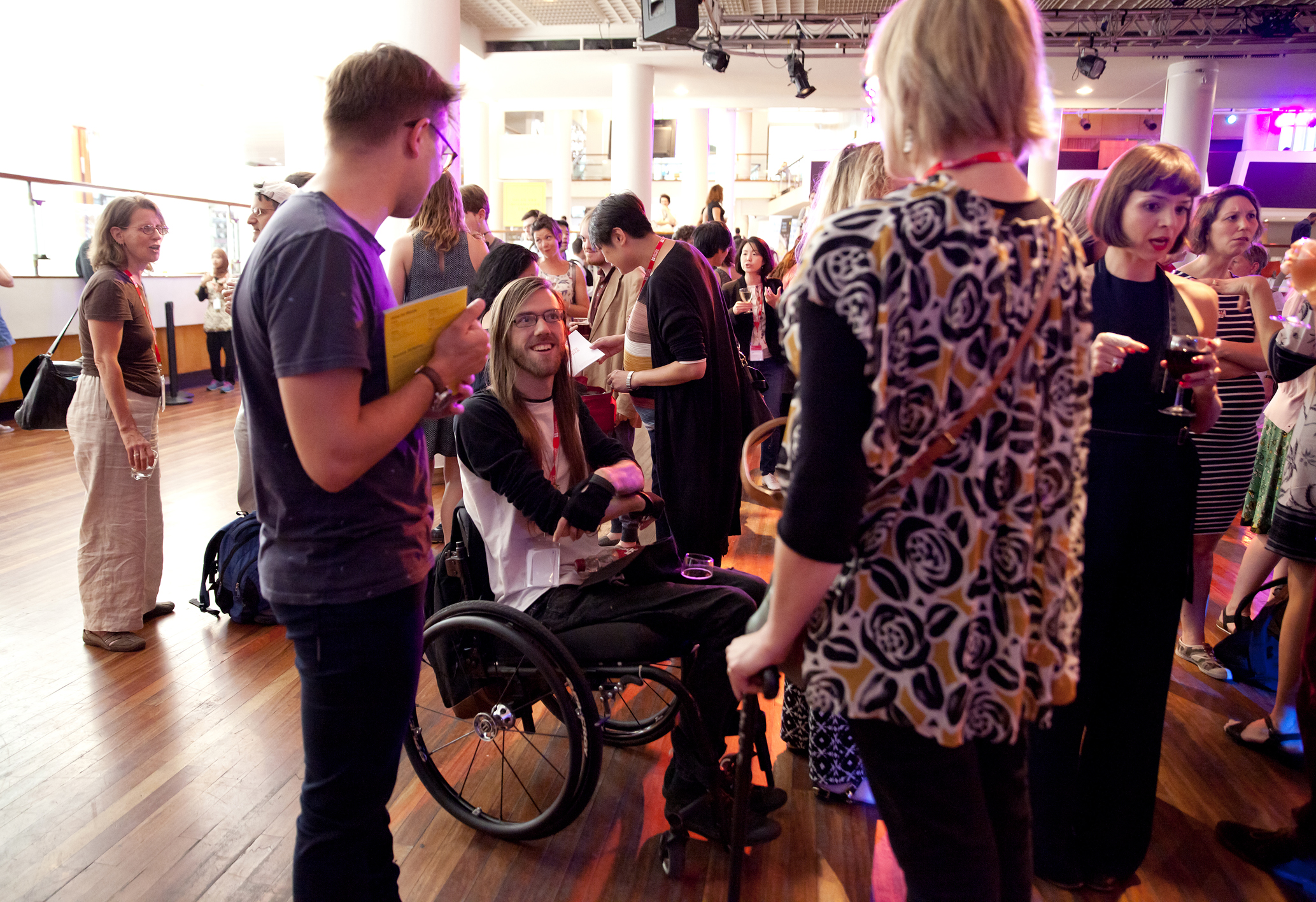 a group of people are talking to each other in a crowed at a launch event. in the centre is a wheelchair user