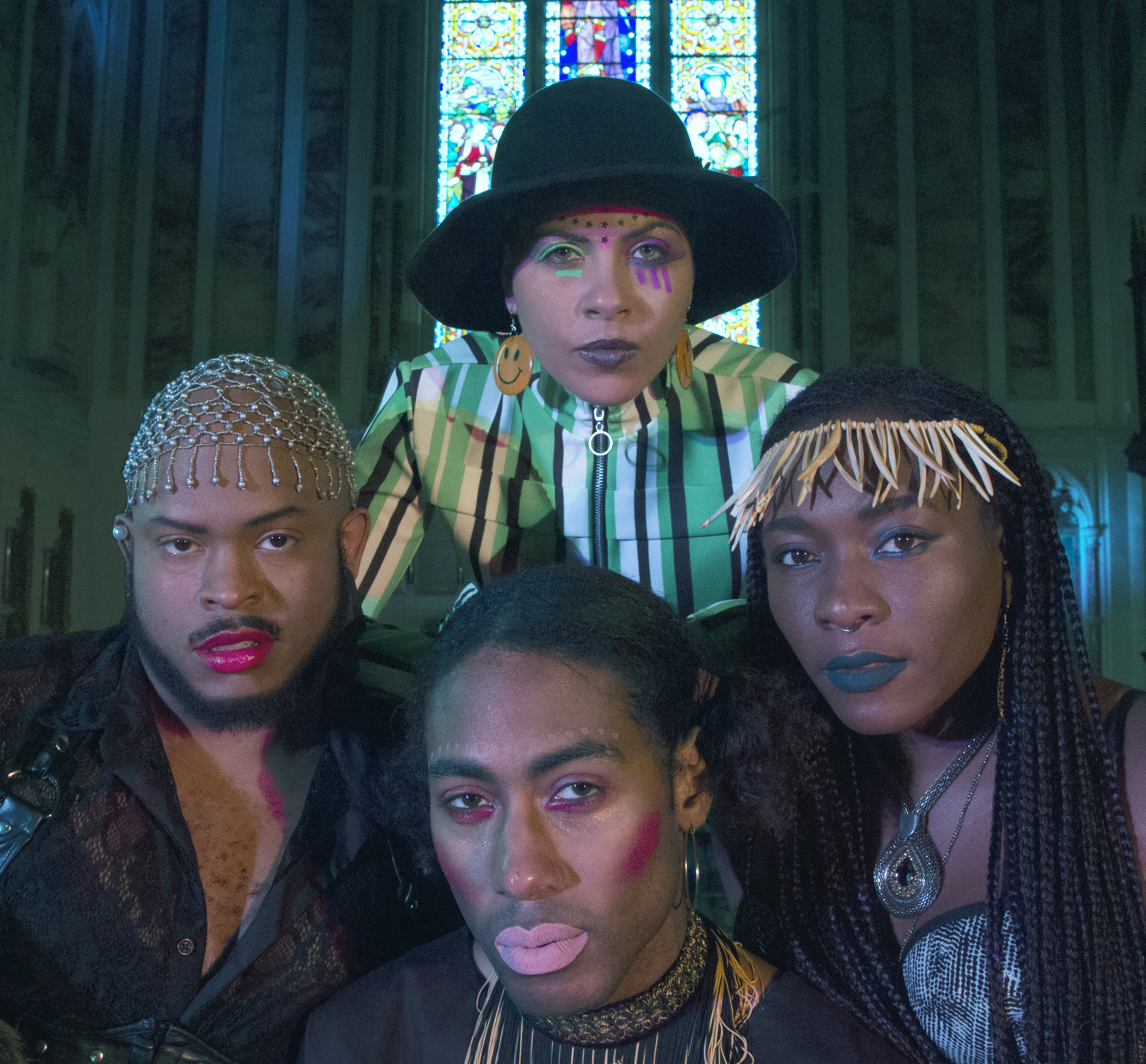 Four people of colour facing the camera standing in a church with a stained glass window in the background. They are wearing colourful costumes, make-up, hats and jewellery.