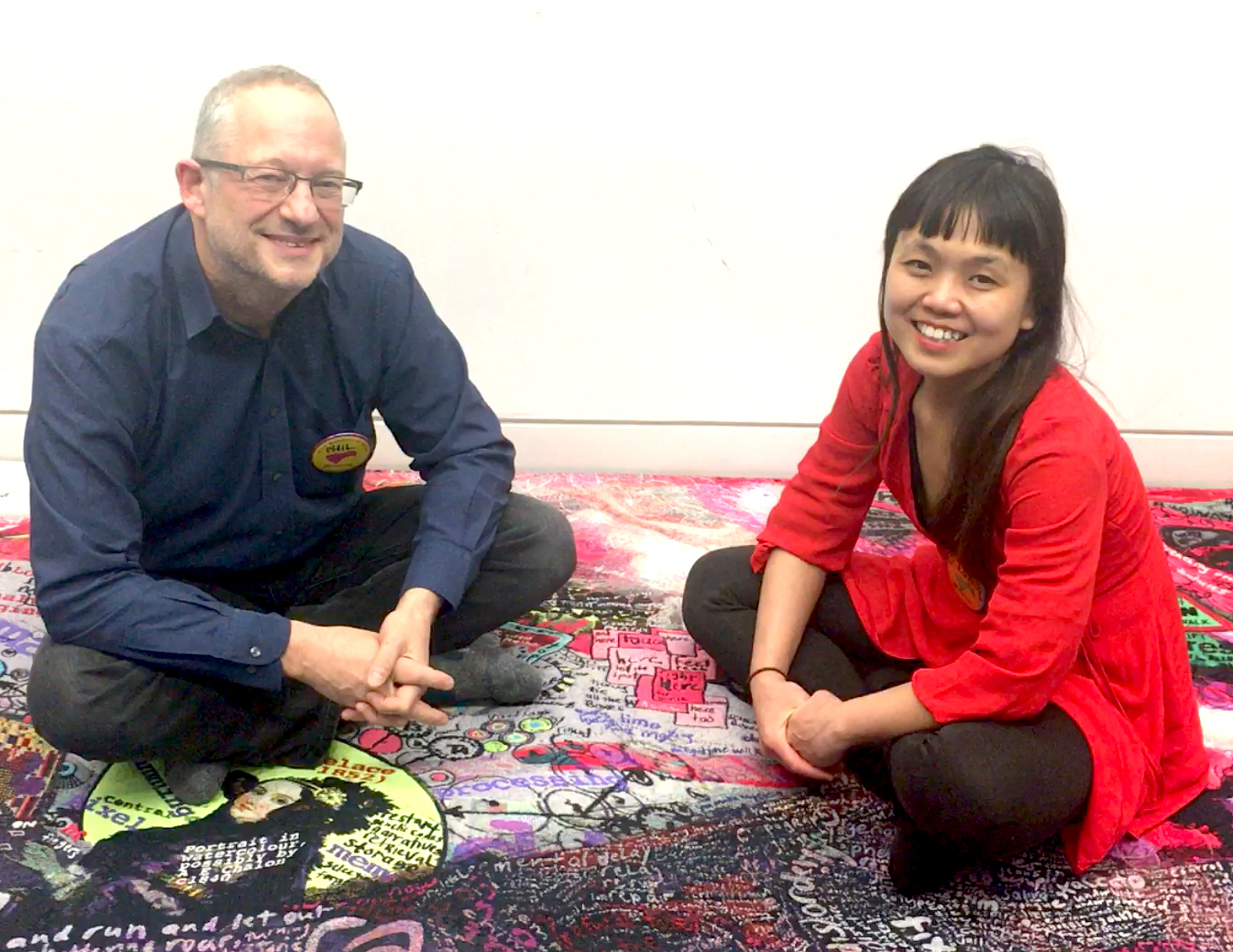 a man and a woman sitting on a mat.