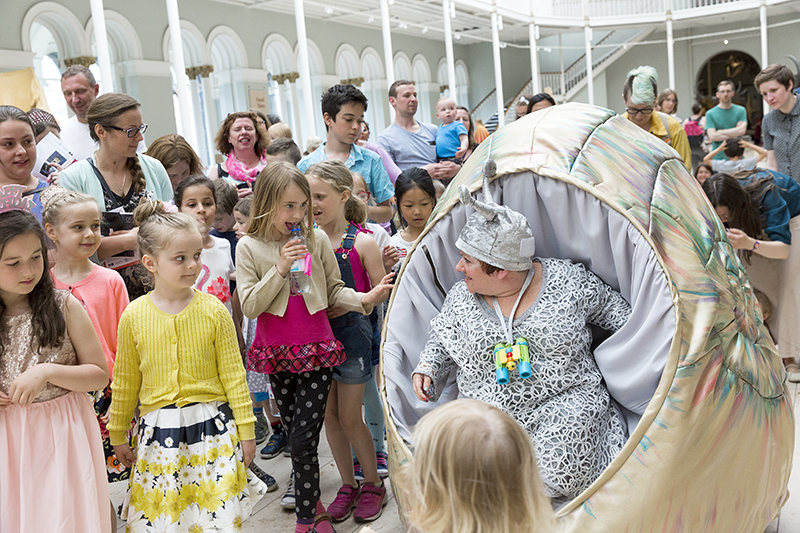 A lady in a snail costume and a group of children surrounding her.