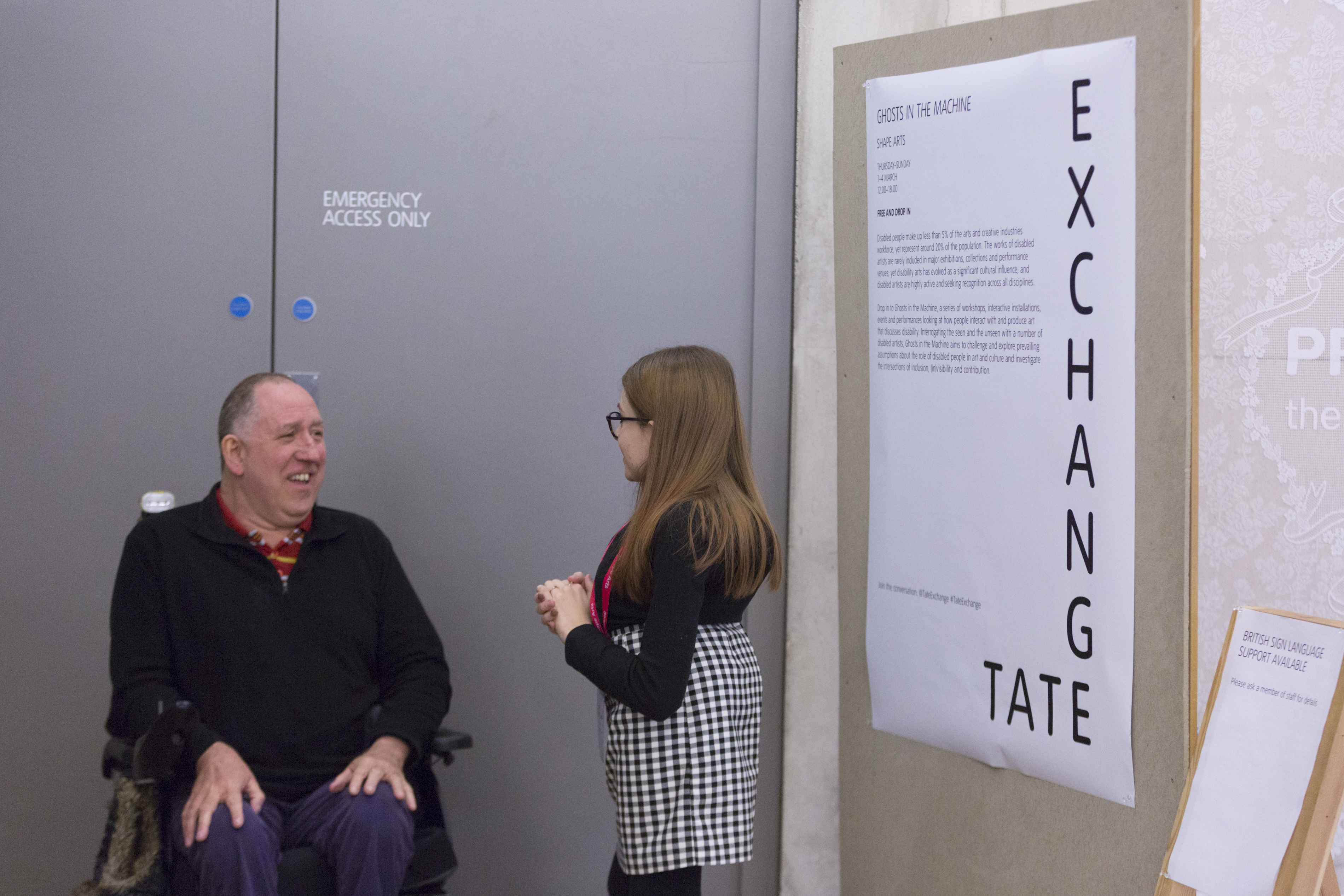 a man sits in a wheelchair to the left of the frame talking to becky dann who is wearing glasses with a black top and skirt. standing in front of a sign that says 'tate exchange'