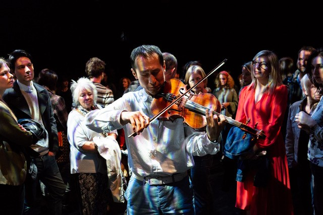 A crowd standing in a semi circle looking at a man playing the violin