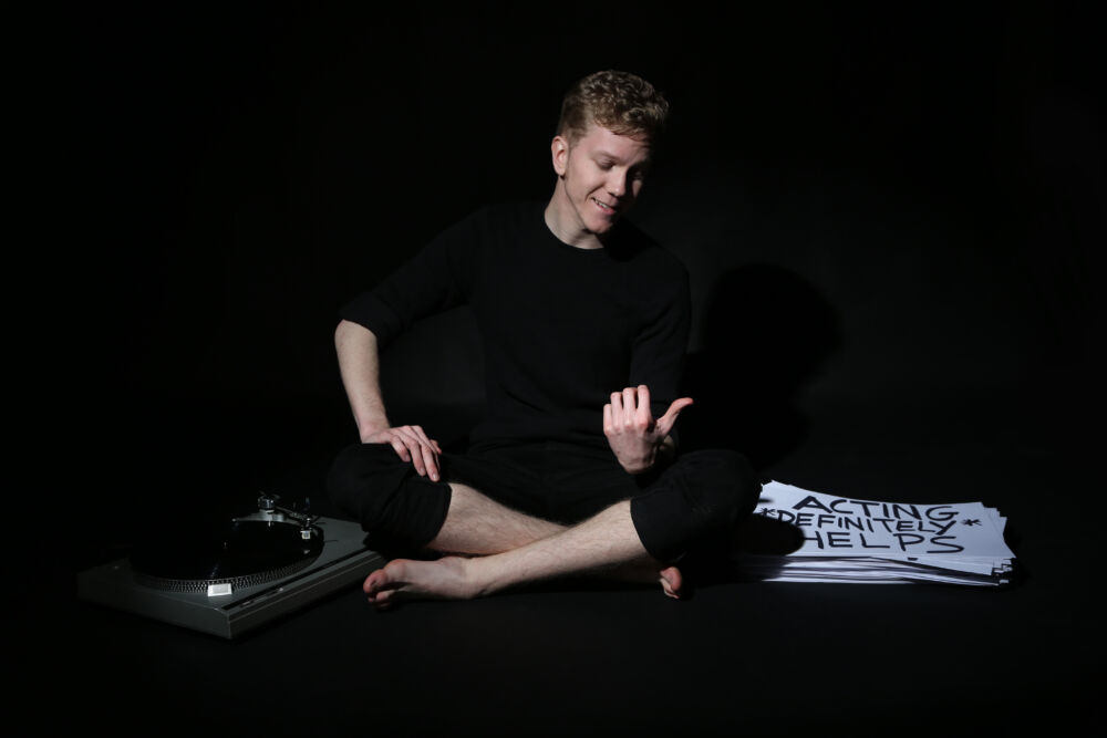 A man dressed in all black pointing at a stack of words which is by his side. there is also a music turntable on his right.