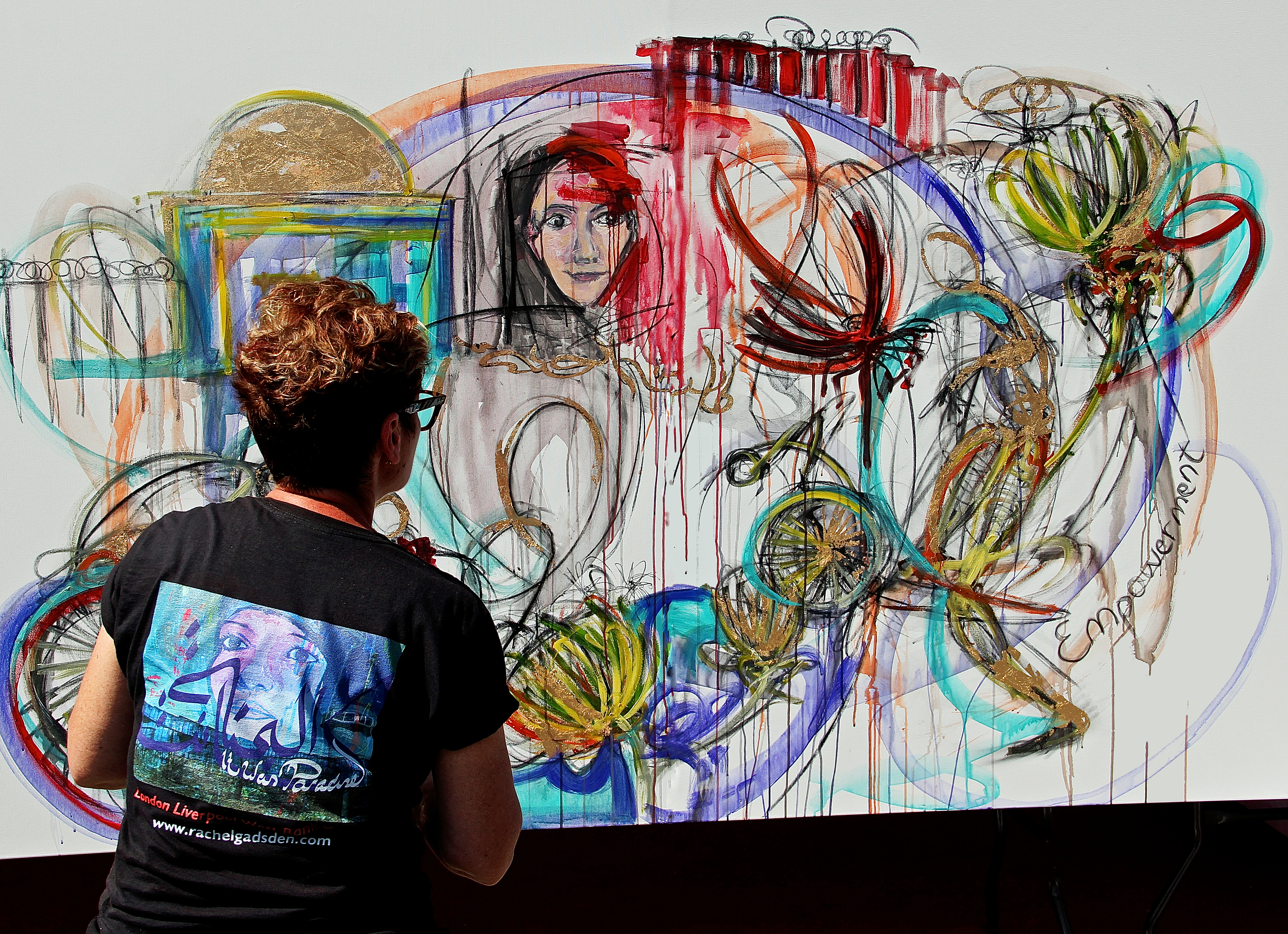 A woman facing her art looking at the details of her work. She is wearing a t-shirt.