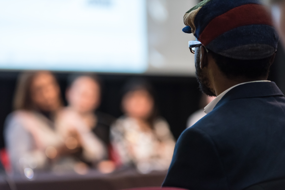 We see the back of a person's head who is wearing a hat. They are facing a panel discussion which is in the blurry background but we can just about make out three people.