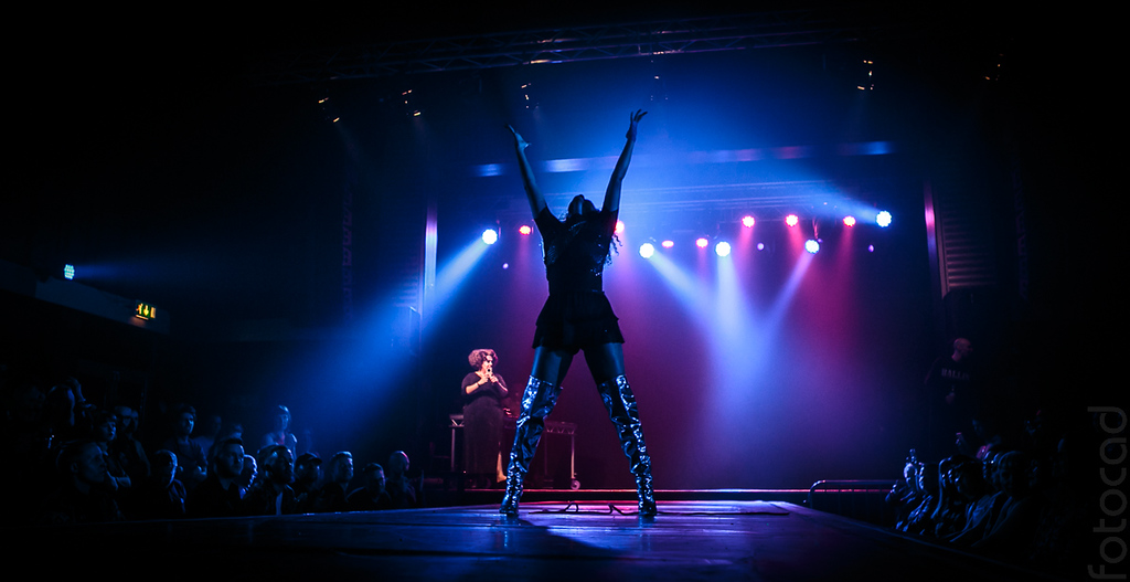 picture of a woman with her hands up in the air. there is dark lighting in the area