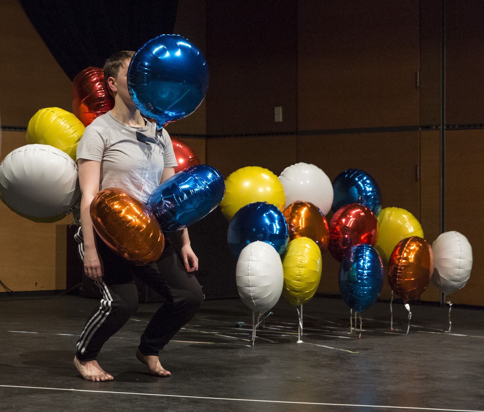 A young woman wearing casual sports wear, barefoot, standing knees bent, is surrounded by colourful helium balloons which are floating around her, covering her face