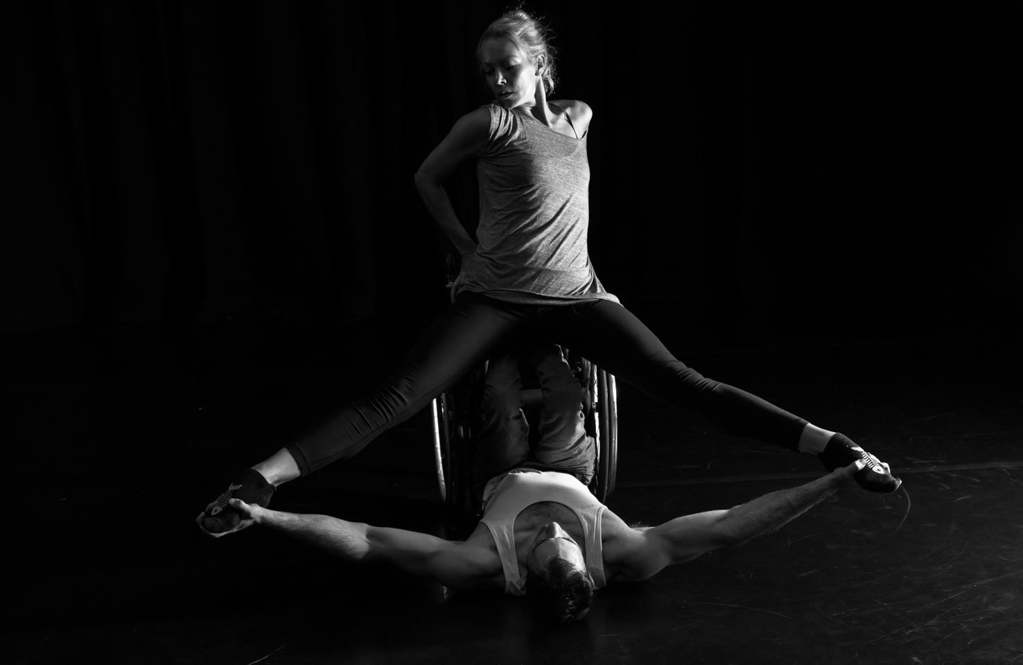 Two dancers performing. Joel is in a wheelchair lying on his back, with his arms extended. Eve is above him balanced on the overturned wheelchair, her legs supported by Joel's arms.