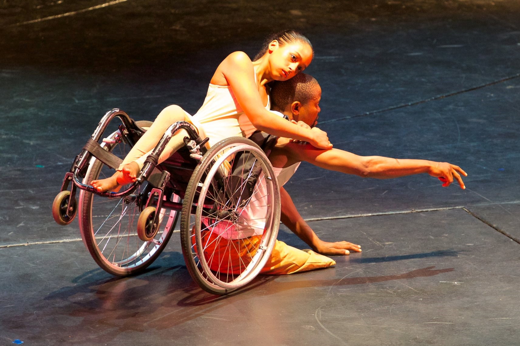 Two dancers one is a wheelchair user and the other is by their side. They are dancing in this picture