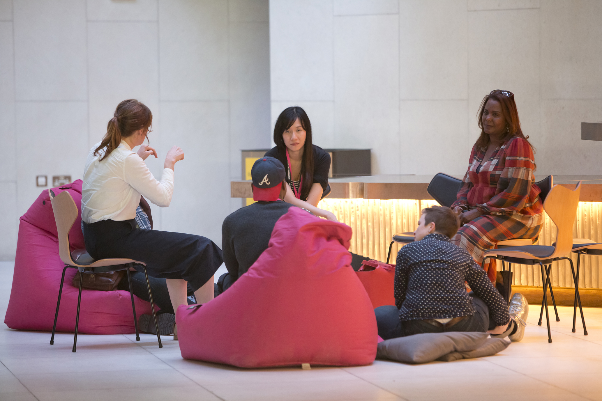 Sandie is in the middle of a group conversation with four people sat on chairs, cushions and beanbags.