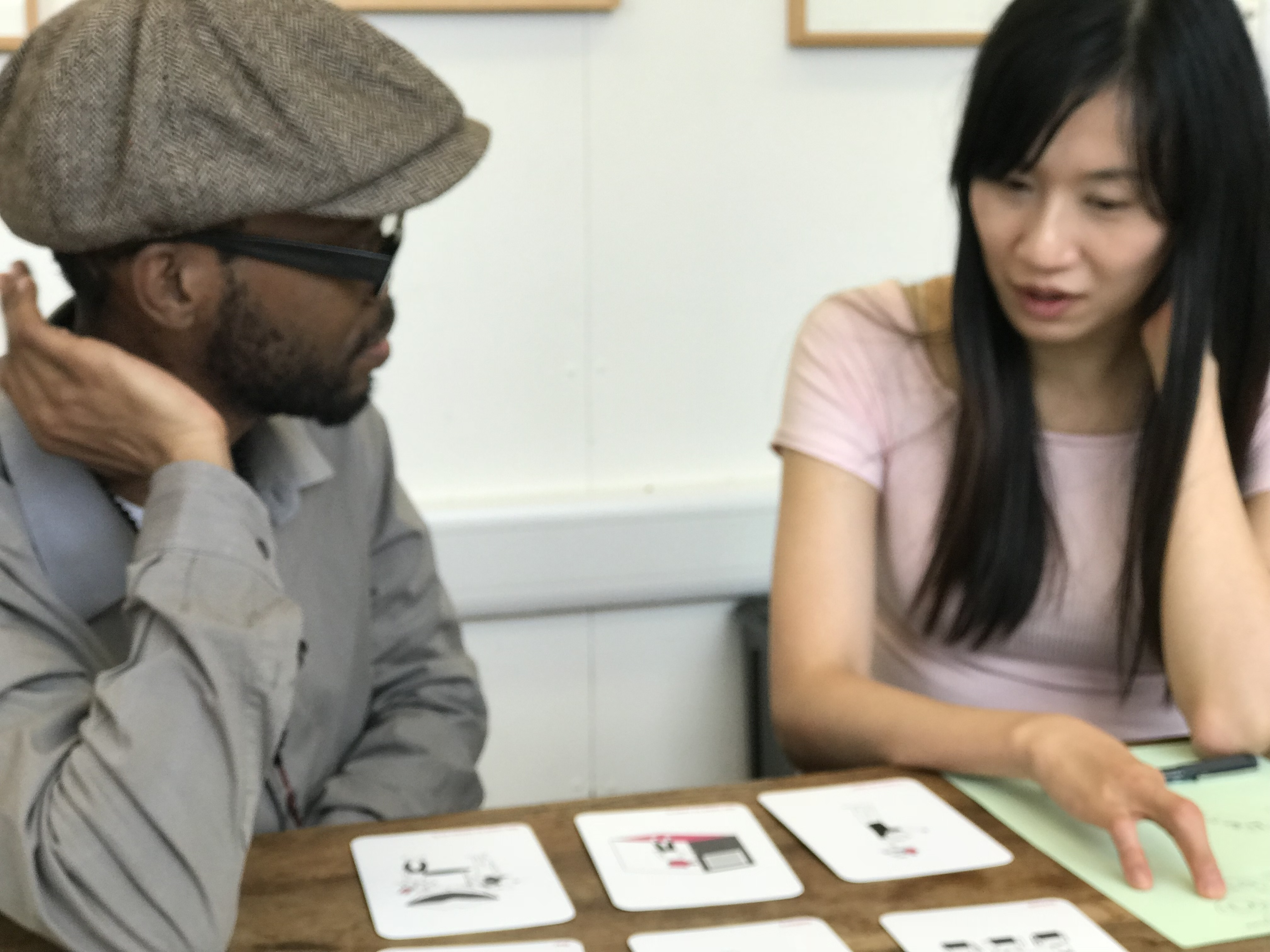 Close up of two people sitting at a table talking. In front of them they have a few cards laid out and a piece of paper.