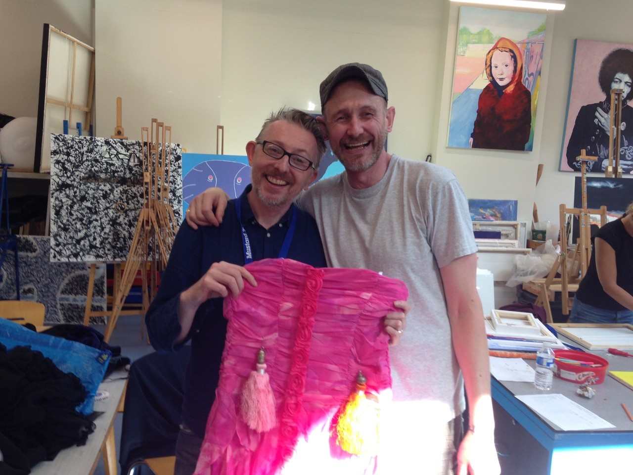 Two men in an art studio smiling and holding up a pink dress, looking directly into the camera.