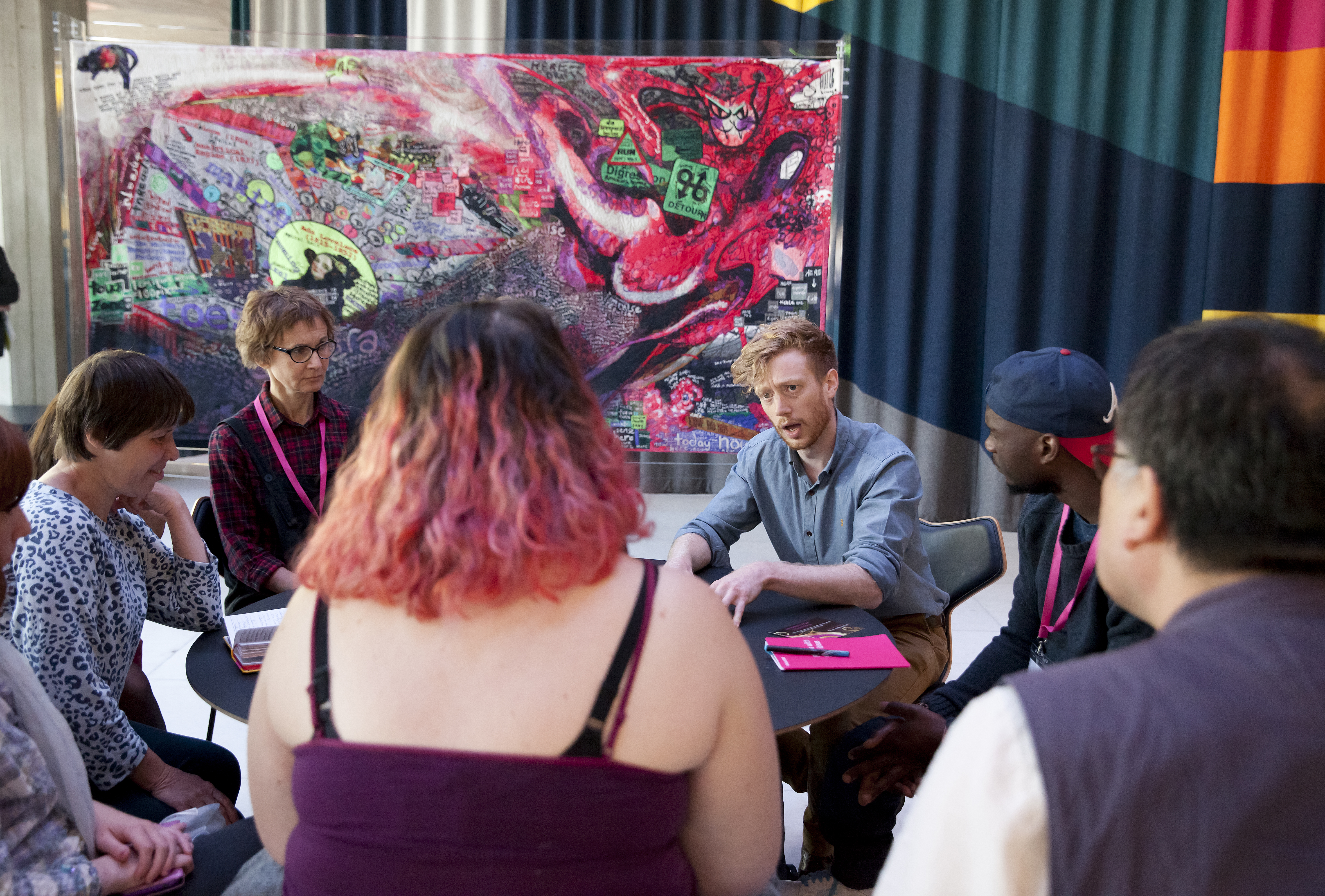 A group of people are sat at a table having a discussion. There is a colourful artwork in the background.