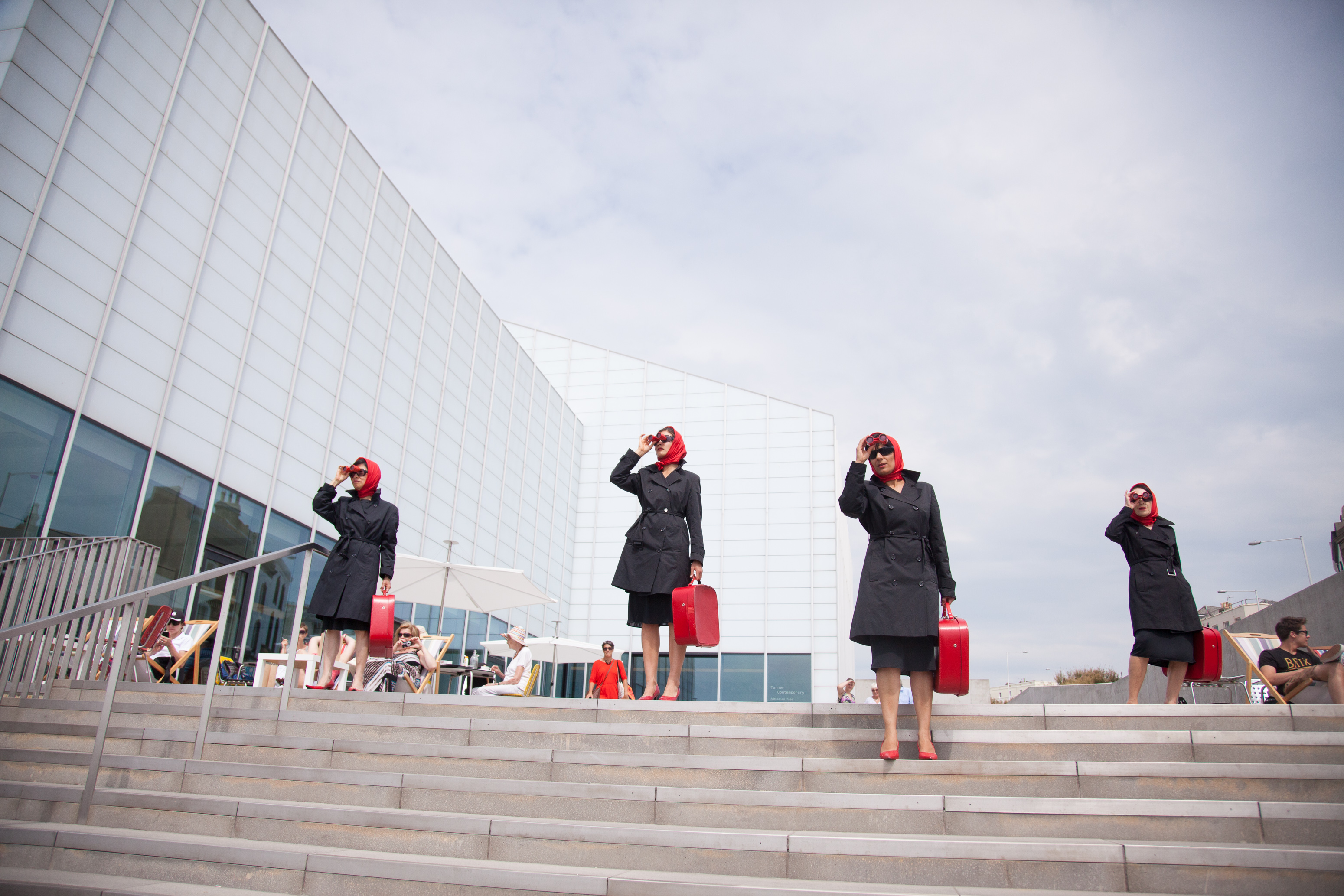 Four women stand on steps outside looking through binoculars, all dressed in the same red head shawl, sunglasses, black coats, black skirts, red heels and carrying red suitcases.