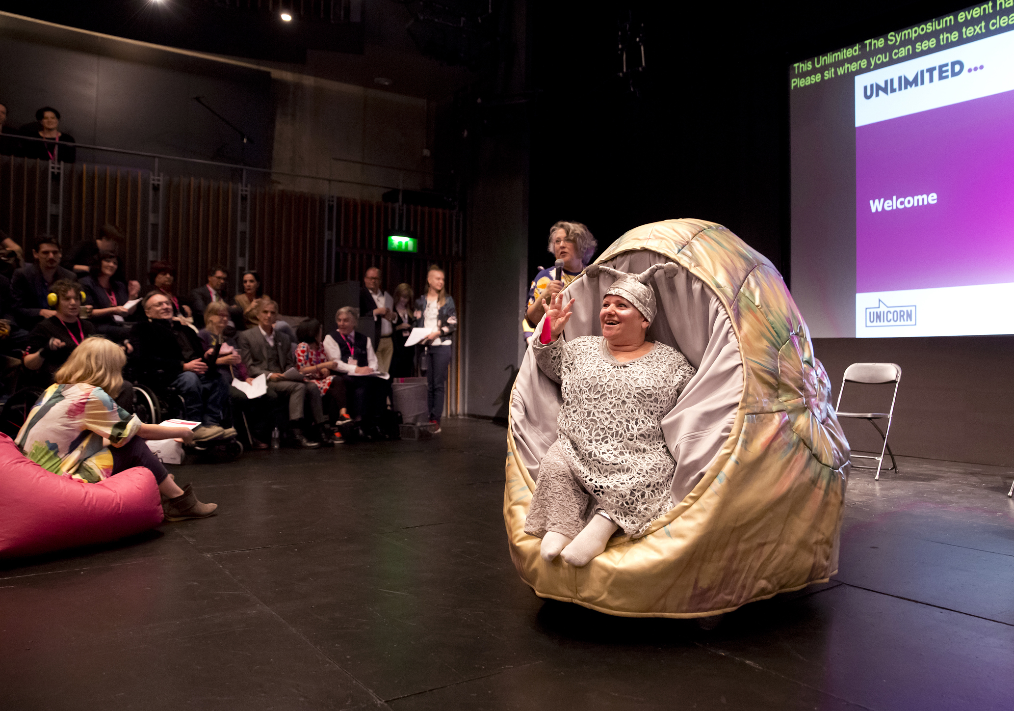 Caroline Bowditch is in a dark theatre space in costume as a golden snail. She is waving in the direction of an audience, whilst Jo Verrent stands behind her with a microphone. They are in front of an Unlimited PowerPoint presentation that says 'Welcome'.