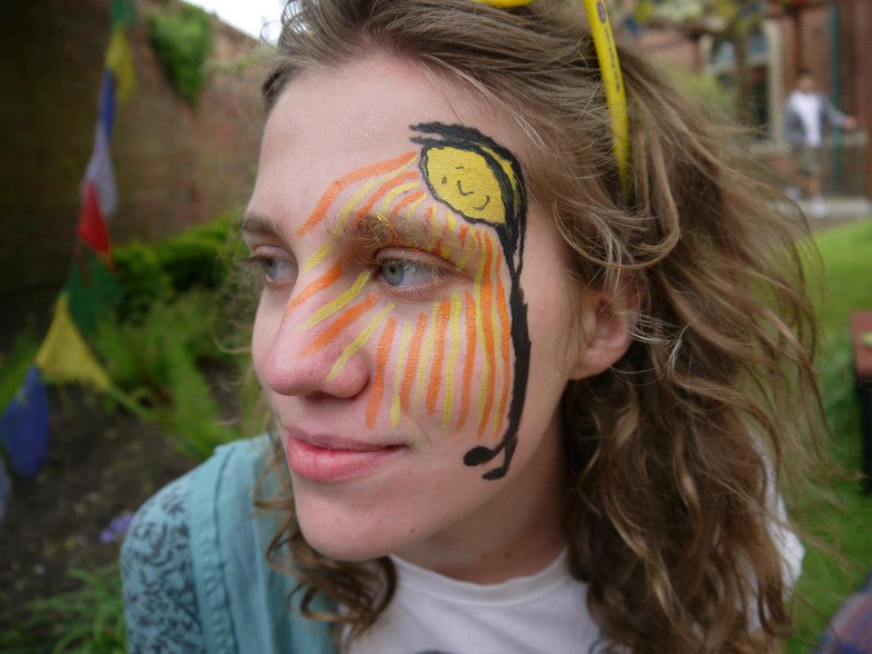 A young woman is looking off-camera to the left. She has a face-painting of a smiling sun streaming its rays of light in orange and yellow.