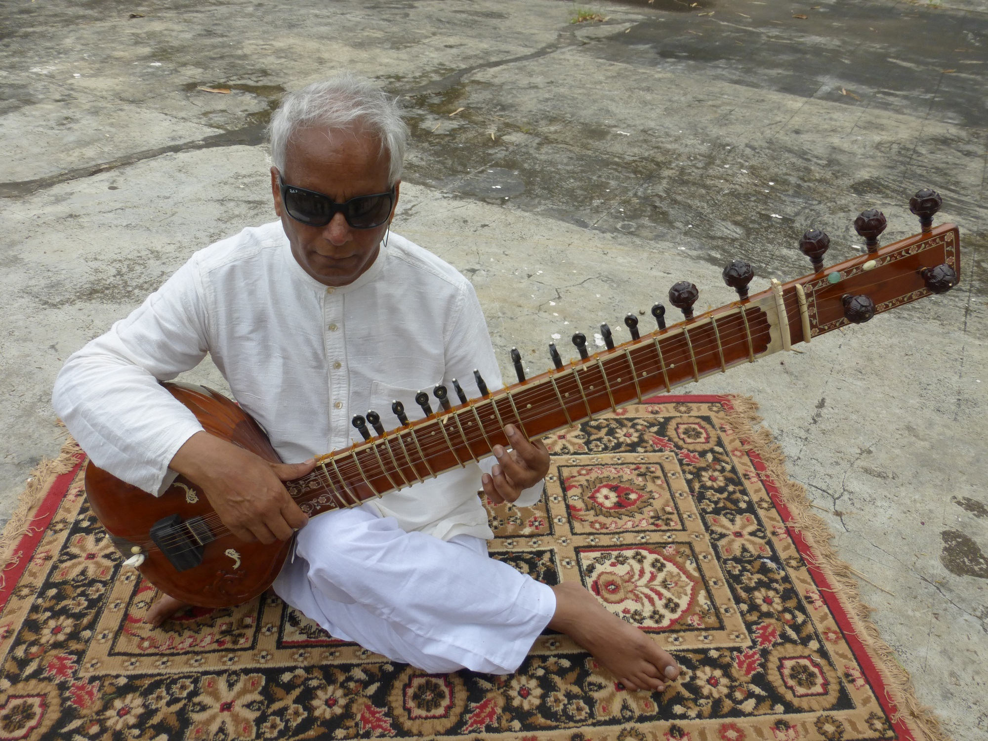 Baluji is sat on a mat holding a sitar.