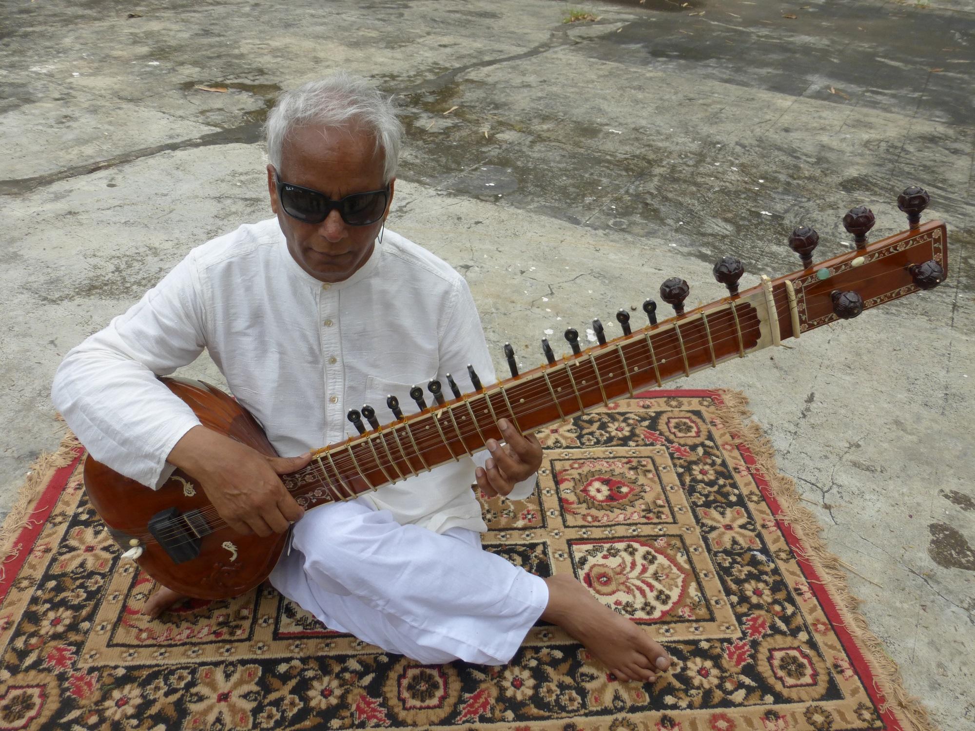 Baluji is sat on a mat holding a sitar.
