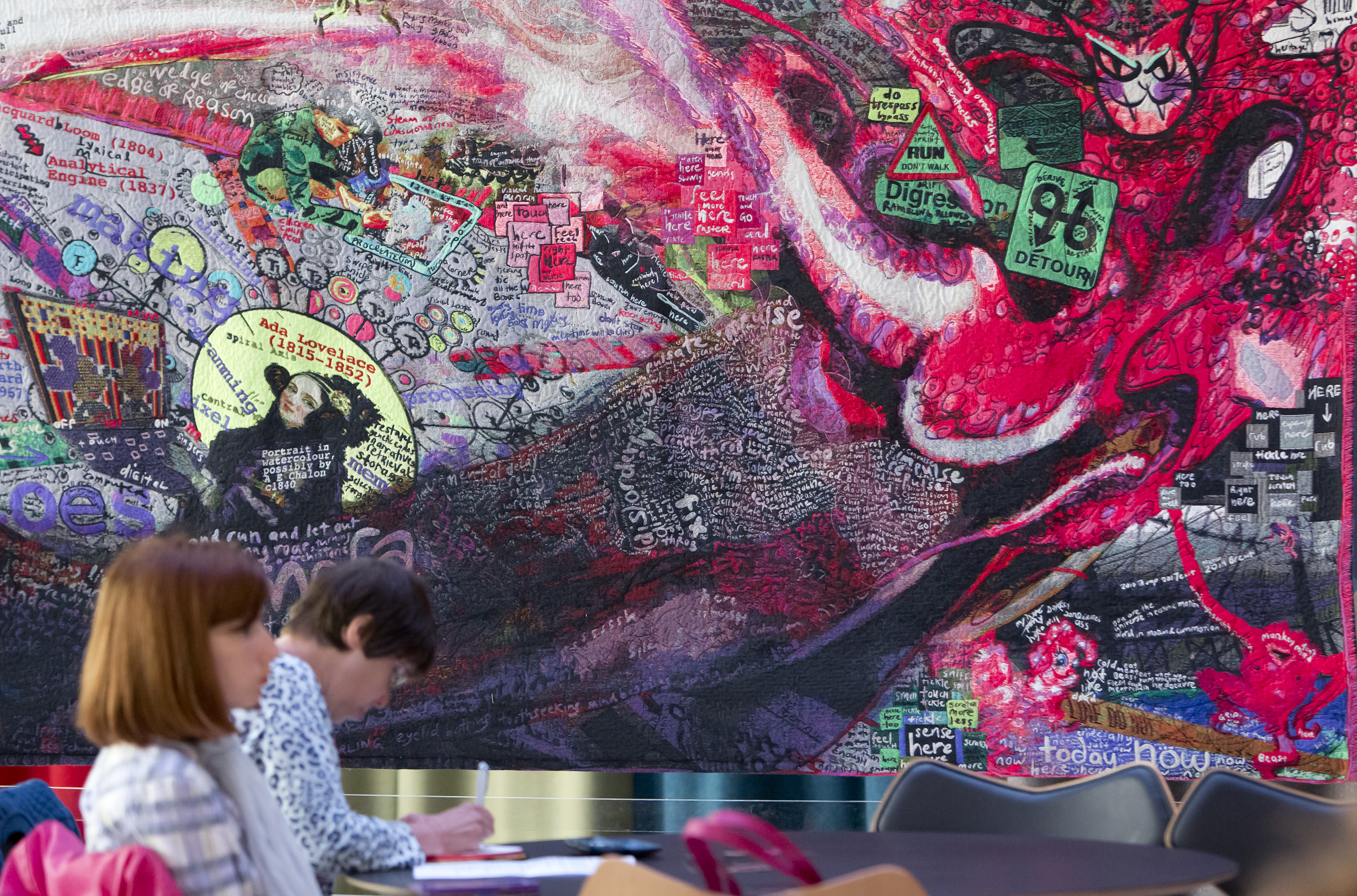 Two women are sat at tables in the foreground against a backdrop of an intricate and convoluted tapestry of collages and vibrant colours, which is intended to illustrate a voyage into the artist's mind.