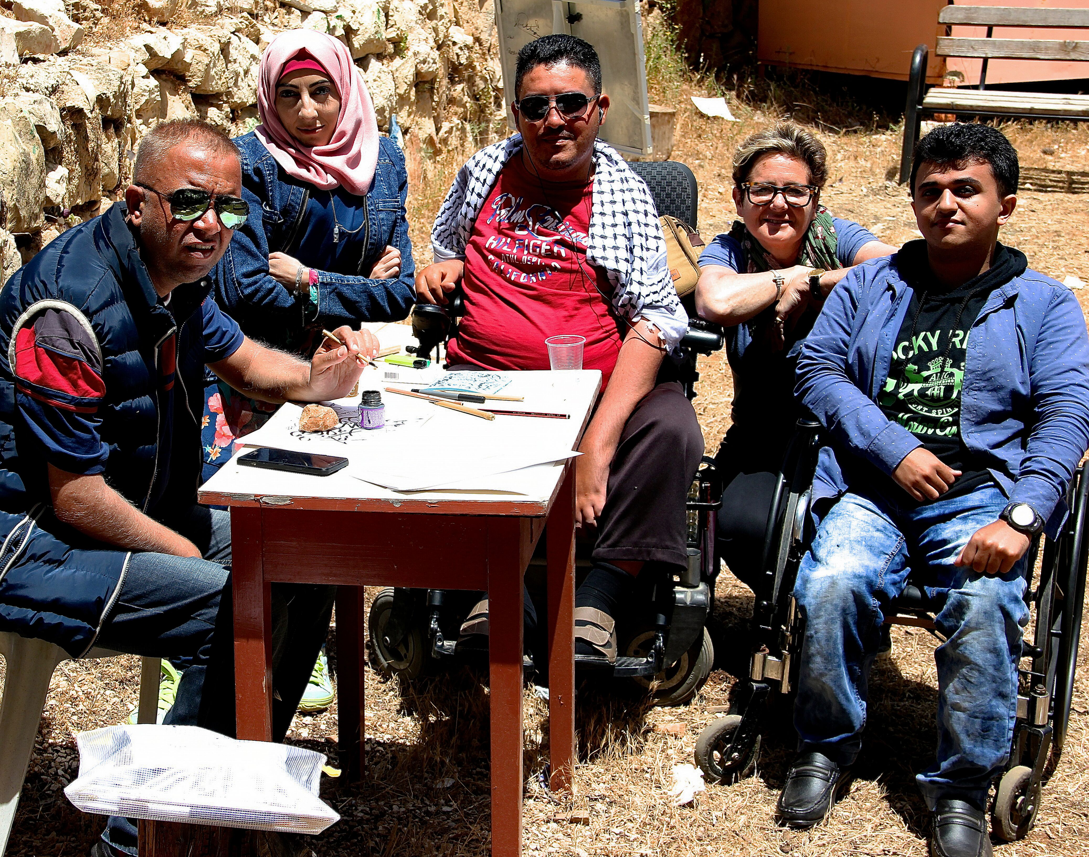A group photo where Rachel is sat around a table with artists Ali Saied Ashour, Amna Hussein, Hosaam Khdair and Mahmoud Abu Daghash. They are working outside in the sun and are all looking directly into the camera.