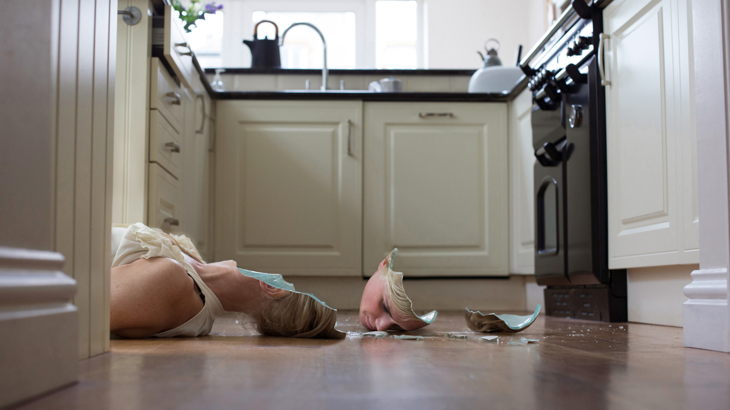 A blonde woman lies on the floor with her head cracked to pieces and scattered across her kitchen floor, as if she were made of porcelain.