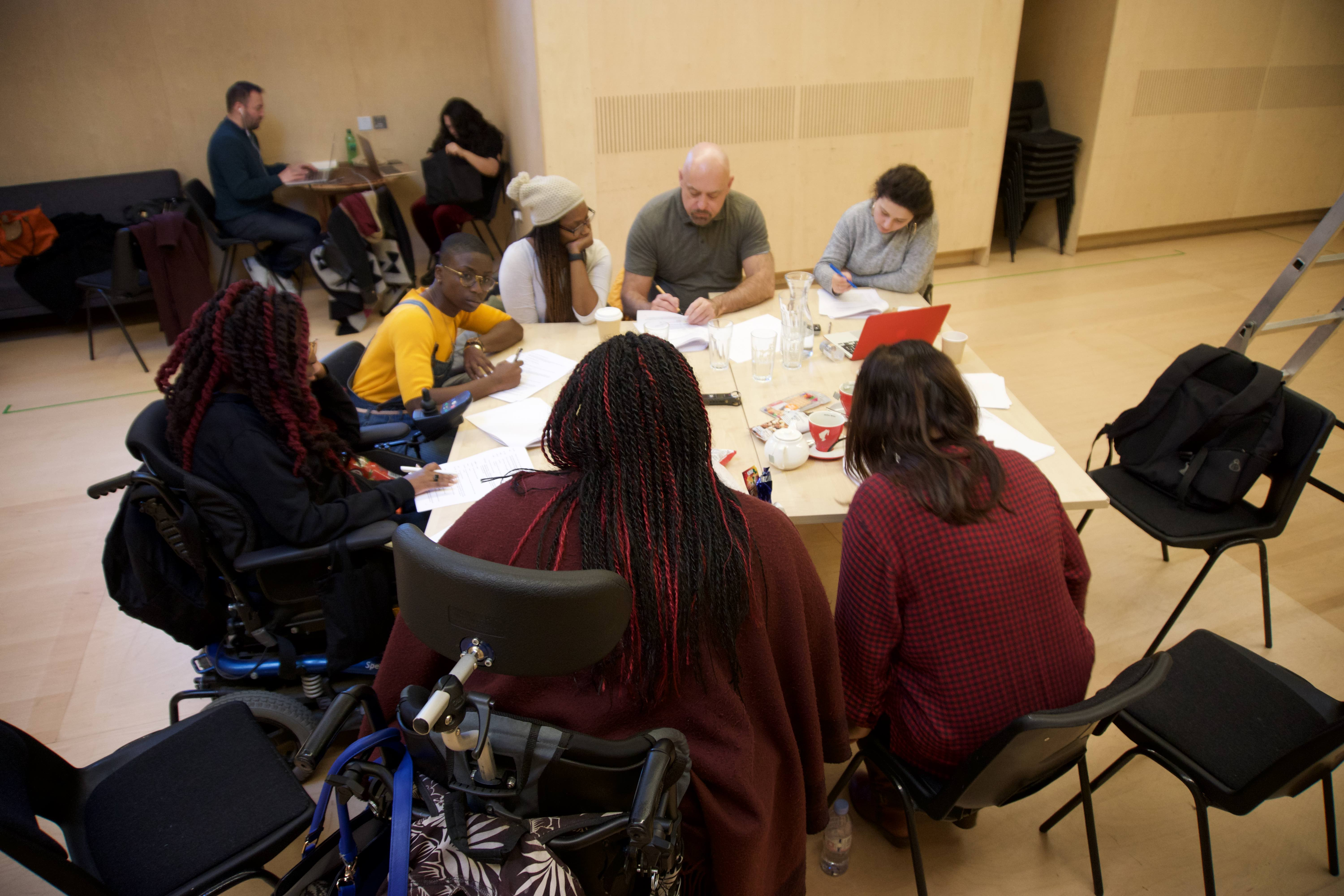 The photo is taken from above looking down on their heads. Seven people of varying ages and races sit around a table, with scripts in hand. They comprise of three actors, two BSL interpreters and the director and writer. The actor and writer are both sat in electric wheelchairs. Everyone's head is down as they work on the scripts in front of them. Two people are sat in a corner around a smaller table both have laptops in front of them.