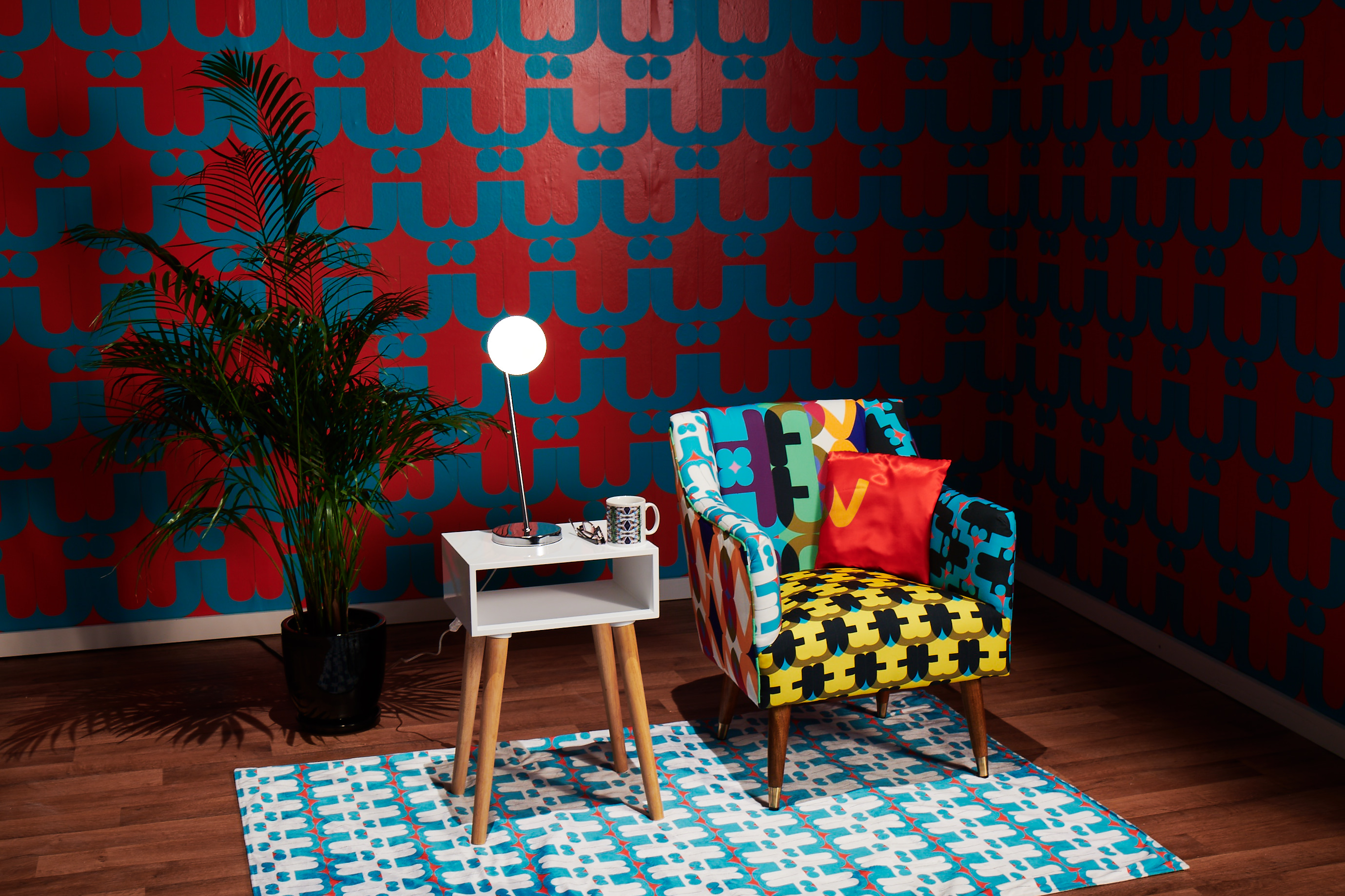 Image shows a domestic lounge in vibrantly patterned furnishings. Centrally placed is an armchair upholstered in a variety of different and colourful fabrics, each printed with a pattern made from mirroring a letter of the ITV logo. Where the fabrics intersect on the backrest, they form the full logo. The chair sits on a similarly patterned rug and the backdrop is vibrantly patterned wallpaper.