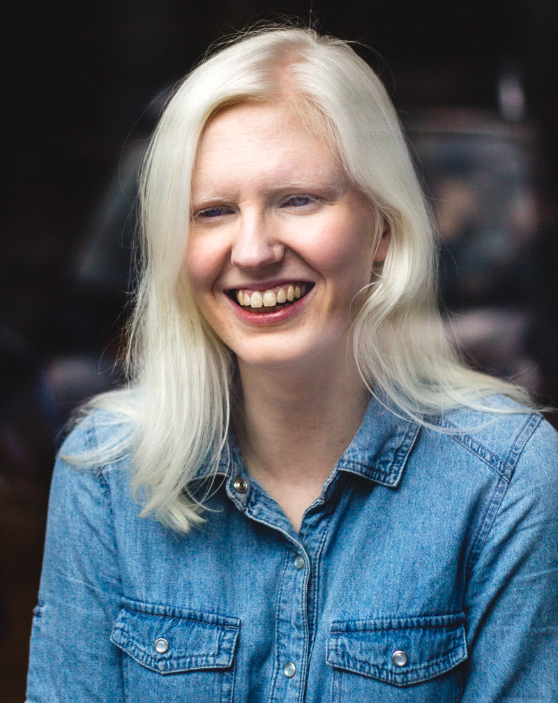 This image shows Ellen Renton, smiling towards the camera against a dark background. She has white hair and blue eyes, and is dressed in a denim shirt. The photo is taken through a window, and some reflection is visible, but no details can be made out.