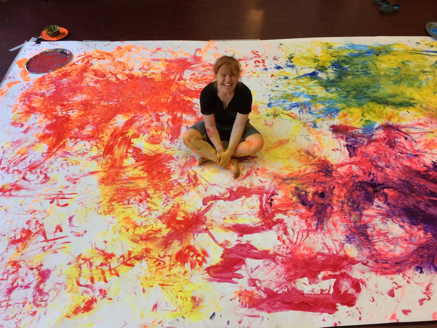 The lead artist, JoAnne Haines, is sitting cross-legged in the centre of a large piece of paper on the floor. The paper is covered with brightly coloured paint in non-uniform patterns. There are finger marks and footprints made with the paint among the patterns. JoAnne is covered in paint and is grinning at the camera.