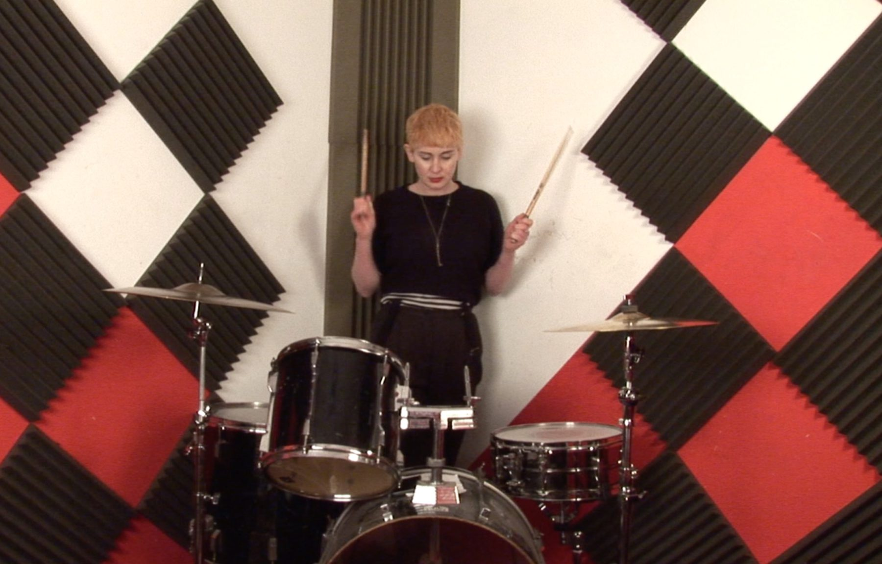 This image shows a person standing playing drums against a checkerboard background