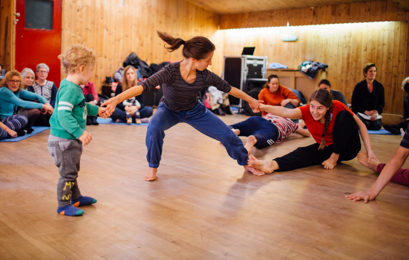 Women is dancing in the centre of a room holding hands with a child and an adult. Audiences sit around the perimeter of the room.