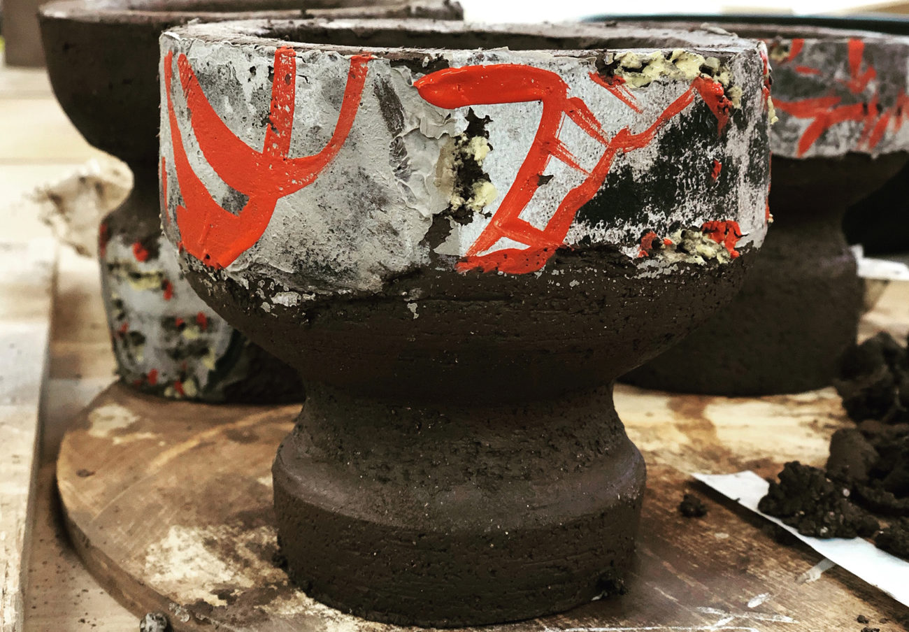 ceramic vessel on a wooden surface, painted with decoration