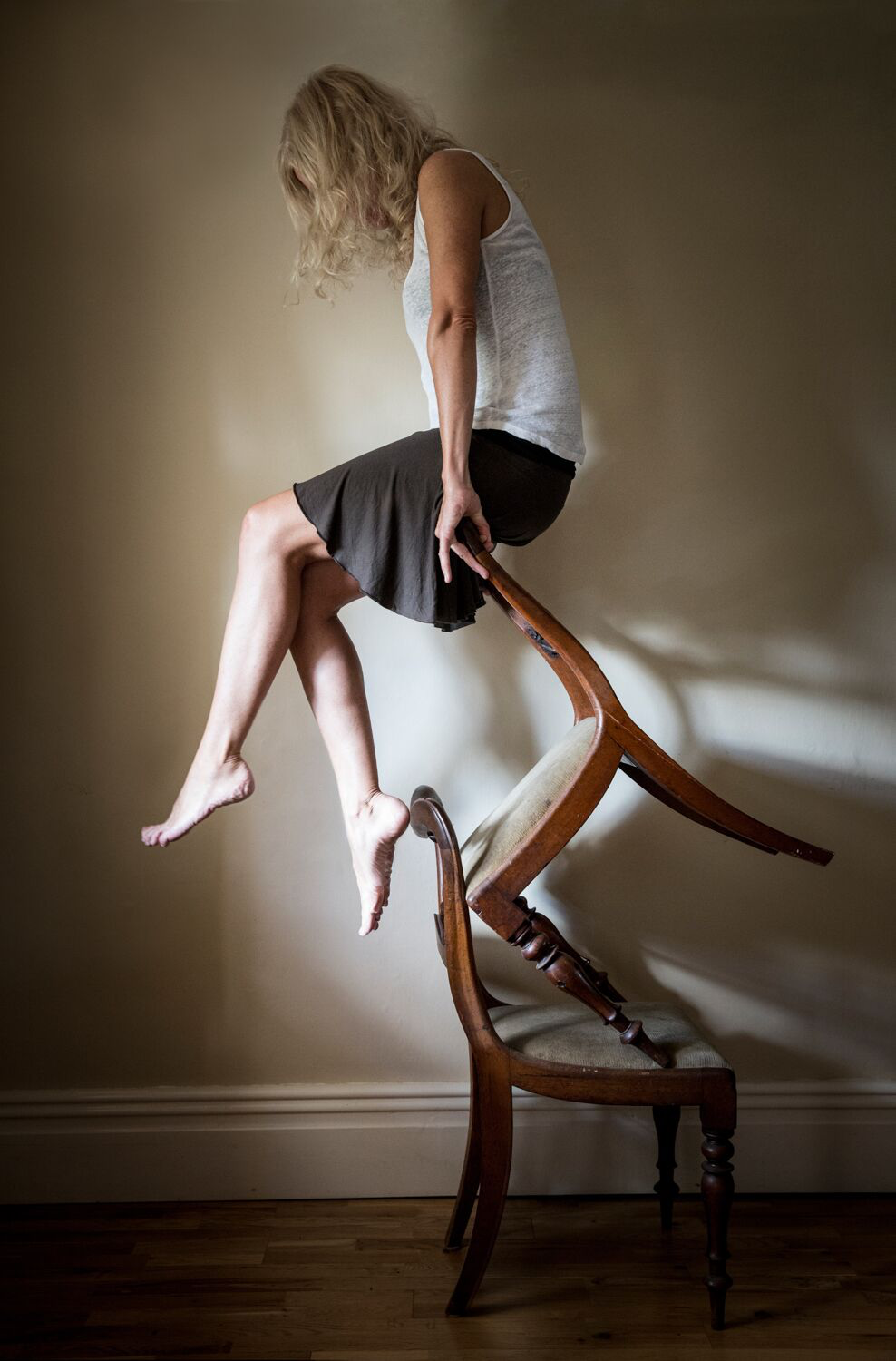 The image shows a woman sat balancing on two chairs precariously stacked on top of each other. From ''In the Mind's Eye'. It depicts anxiety and uncertainty. It illustrates the precarious nature of anxiety; that the slightest thing can set you off kilter. I wanted to challenge the generic head in hands shot, commonly used by the media. I didn't want the series to be too somber. I wanted to incorporate humour and a light-heartedness, to truly represent my experiences.