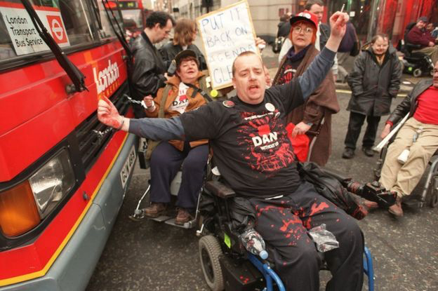 This photograph is of a direct action network (DAN) protestor handcuffed to the front radiator grille of a red London bus. He is a wheelchair user and has other wheelchair users, also protestors around him some of whom are holding placards.