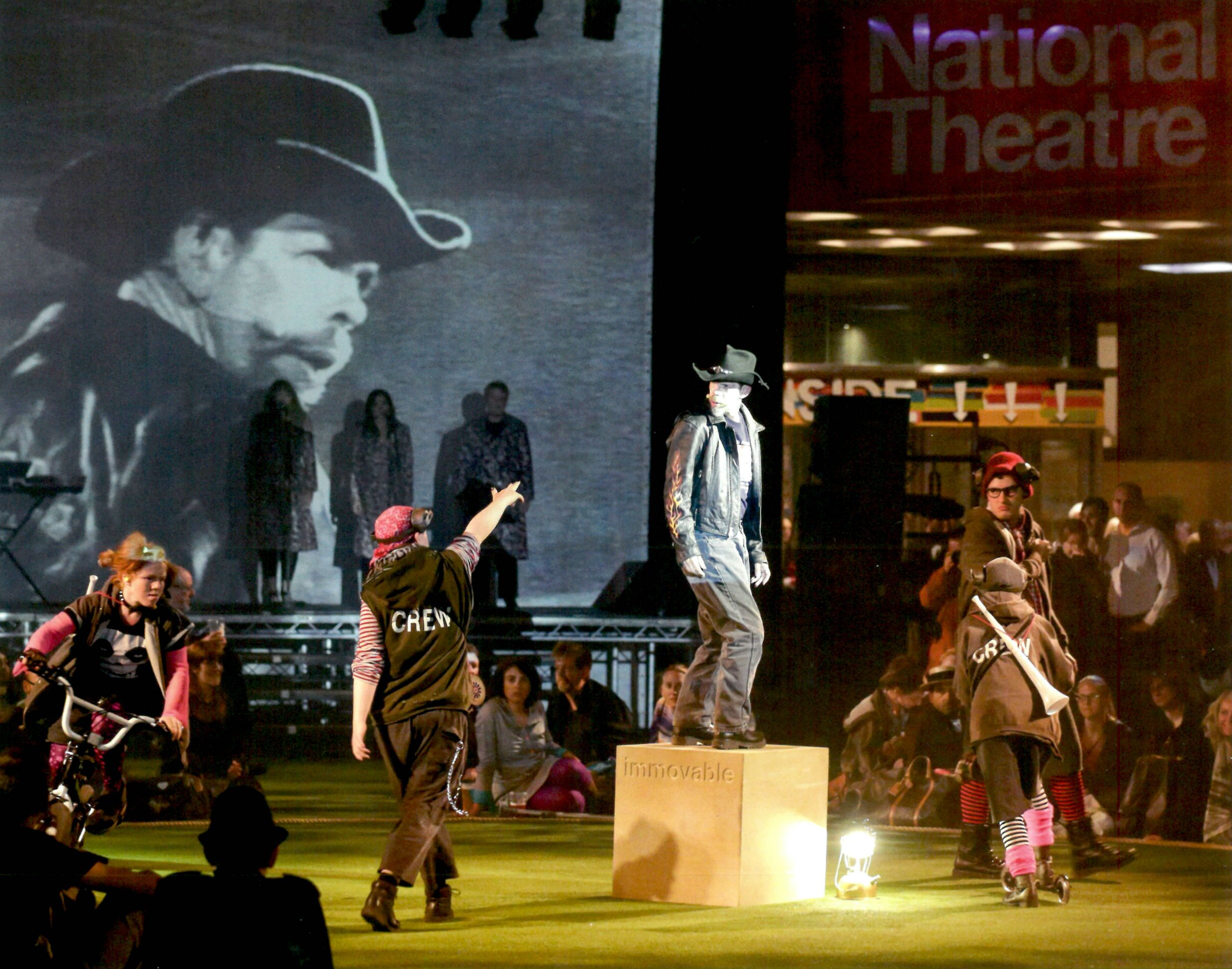 In the centre of a performance space, a man dressed in a black leather jacket, trousers and cowboy hat stands on a cube that says 'immovable' on a green-carpeted floor. He is surrounded by other performers, and beyond them, an audience. The other performers are dressed in a punk-type style and include someone on a bicycle and someone on a scooter encircling him. There is a raised stage behind them onto which a black and white image of a cowboy is projected. Three people stand on this stage as well.