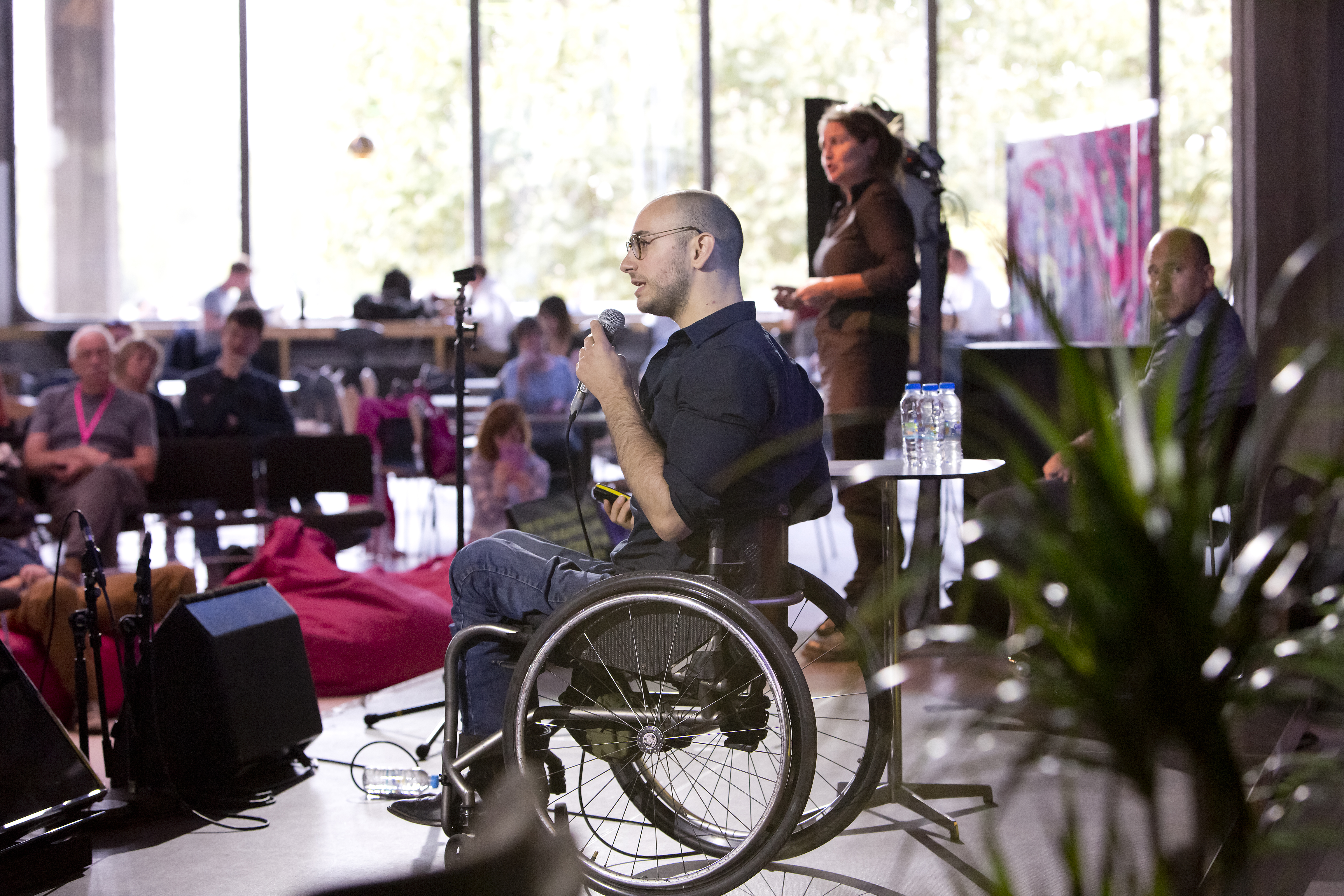 Joel Brown, an athletic, caucasian wheelchair user, holds a microphone and addresses an audience in profile.