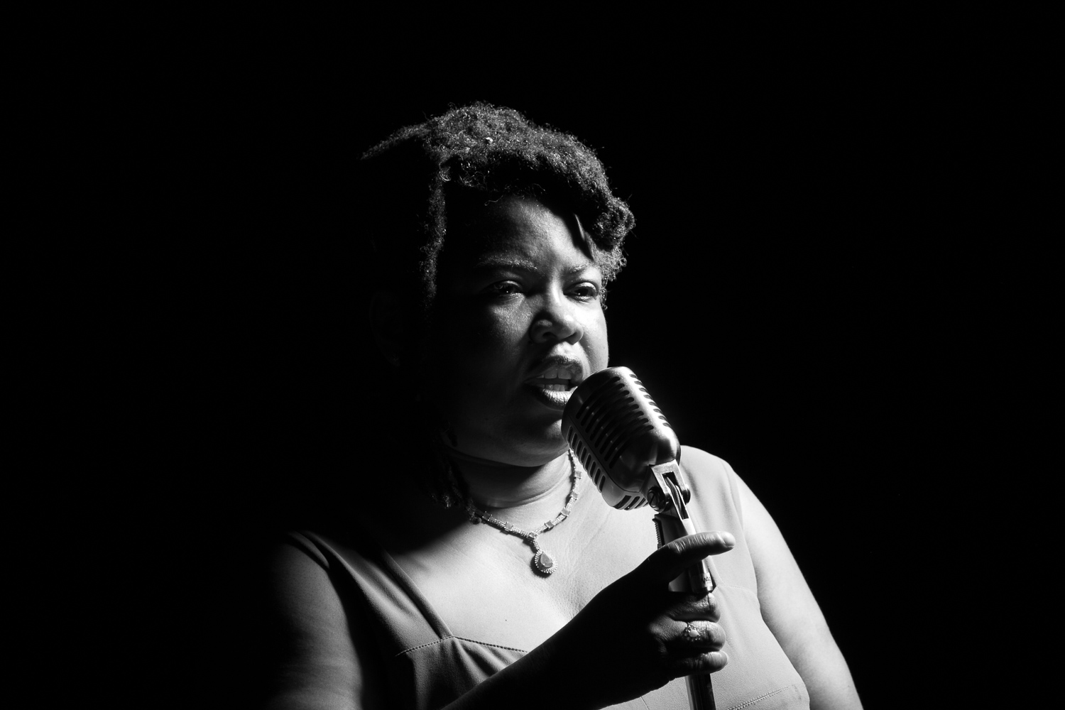 Woman in dark room, illuminated softly and holding microphone with their mouth open