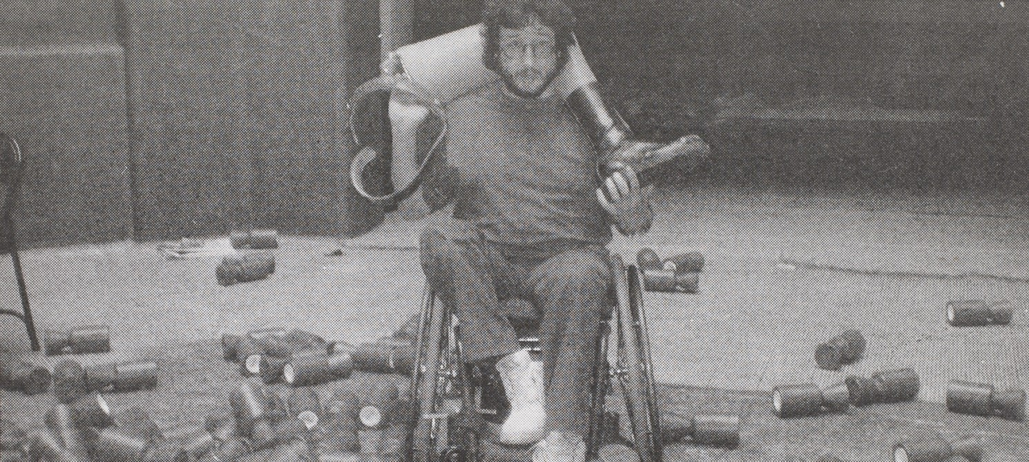 A man, Tony Heaton, is sat in a wheelchair with a prosthetic leg nestled round his shoulders and neck. He is looking at the camera.