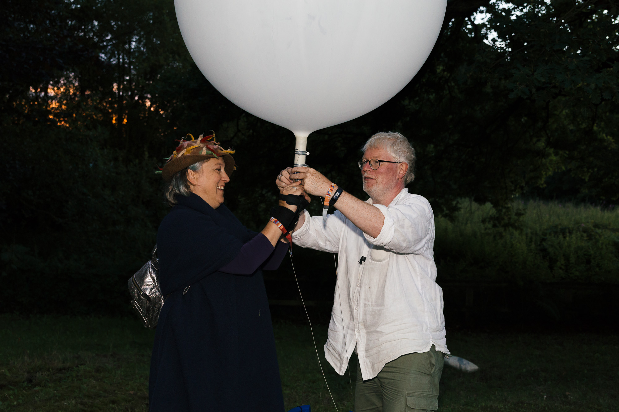 Wide shot of Jo Verrent and artist, Aidan Moesby, holding a very large white balloon up, both clasping their hands around of the base of it. There is a symmetry to the picture in that Aidan and Jo are stood roughly opposite each other in profile, with the base of the balloon situated at the centre of the image. Jo is smiling, whereas Aidan observes the balloon with a look of concentration on his face.