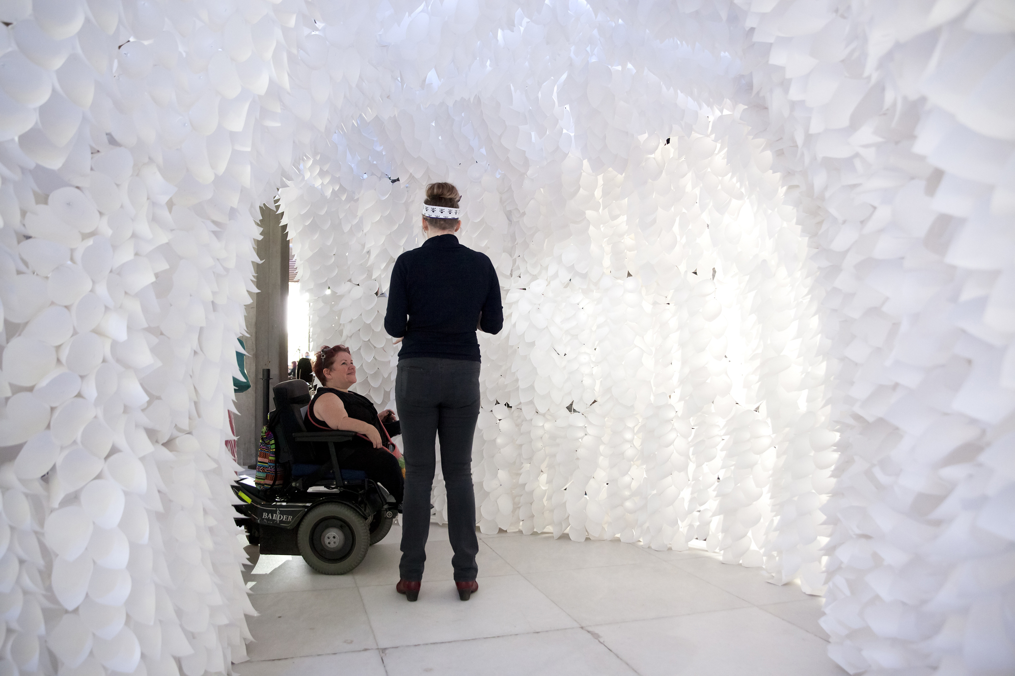 Two Caucasian women, one of whom is a wheelchair user, are within a white archway. Its inside is lined with row upon row of white cones, which appear to be paper, and are lit to appear as though they are glowing.